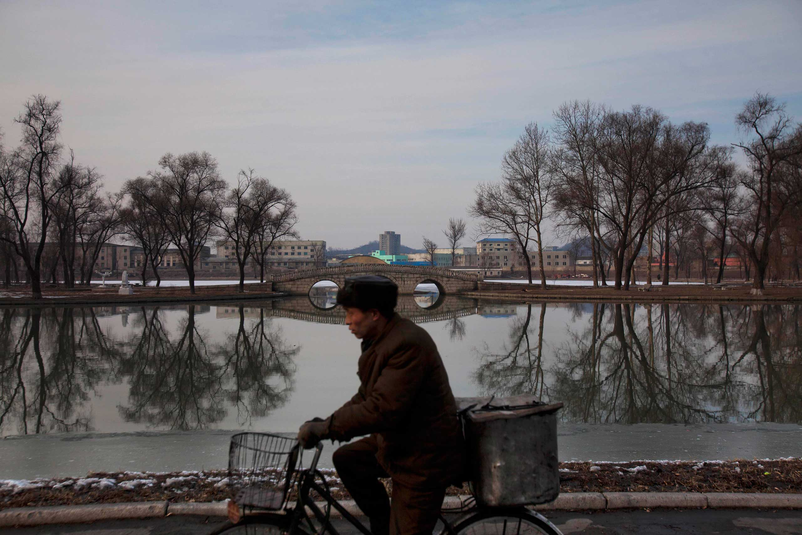 Feb. 12, 2012. A North Korean man rides a bike along the banks of the Pothong River in Pyongyang.