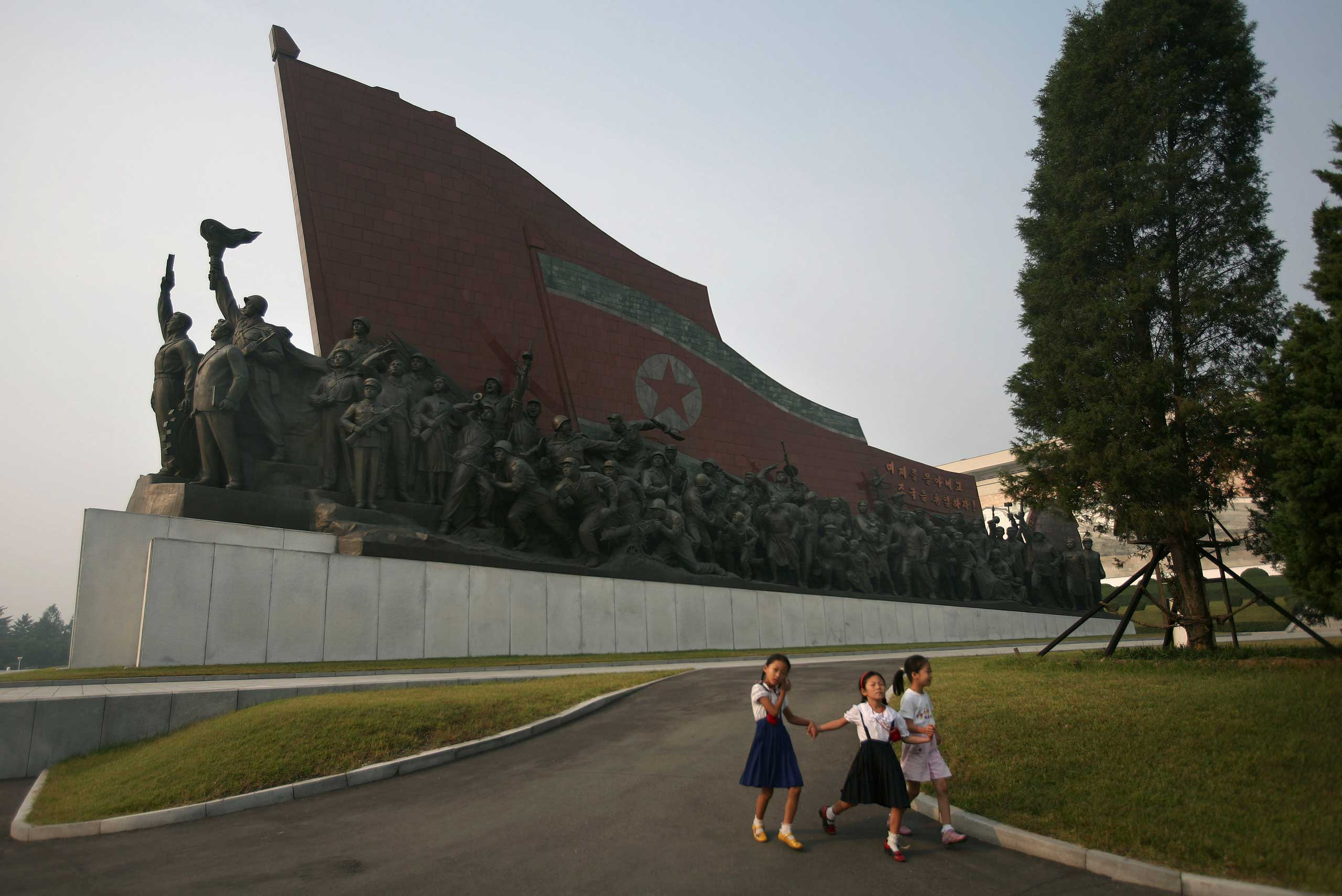 Sept. 17, 2008. North Koreans school girls walk hand in hand past a monument in Pyongyang.