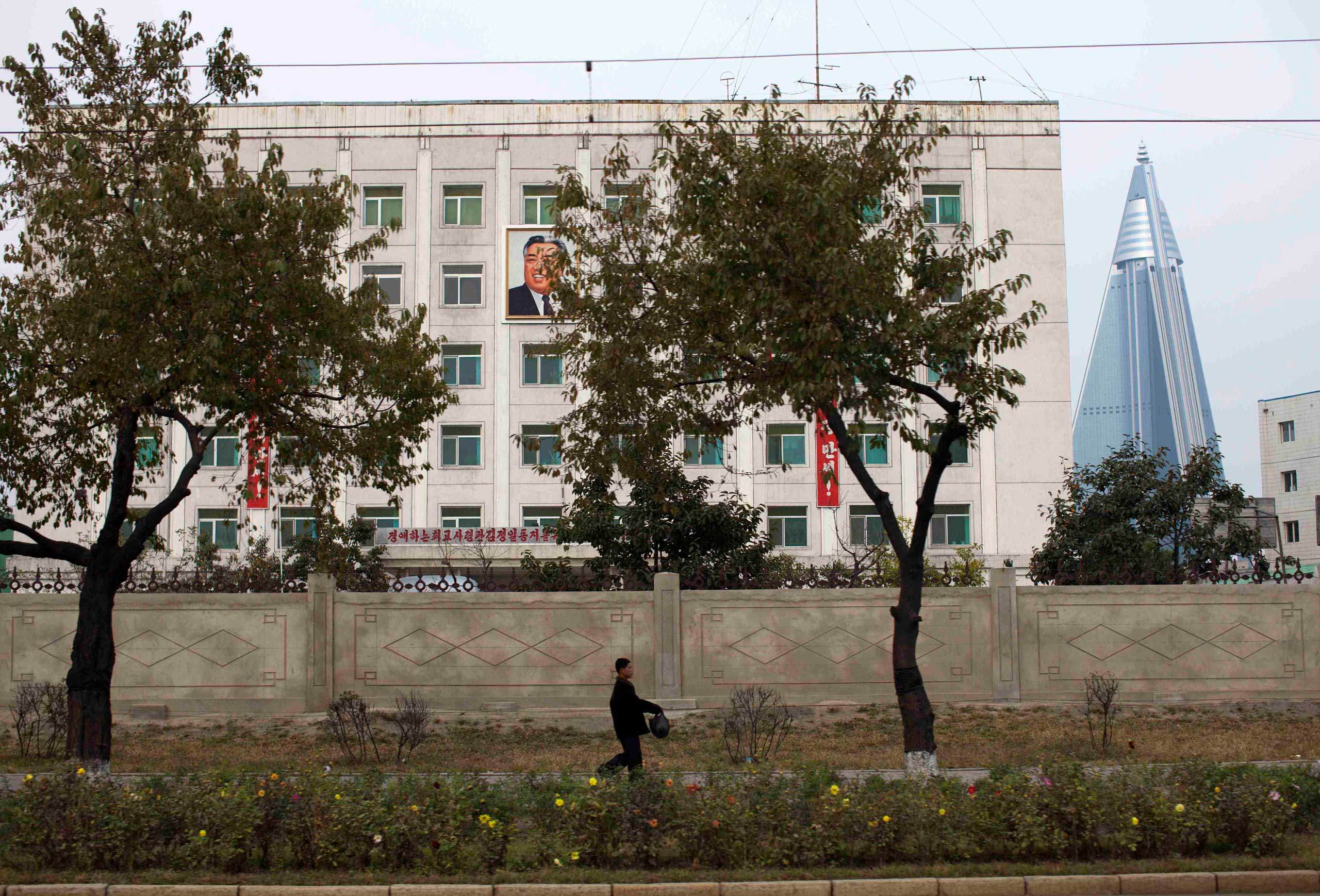 Oct. 9, 2011. A man walks past a building in Pyongyang where a picture of North Korea's late leader Kim Il-Sung hangs on its outer wall.