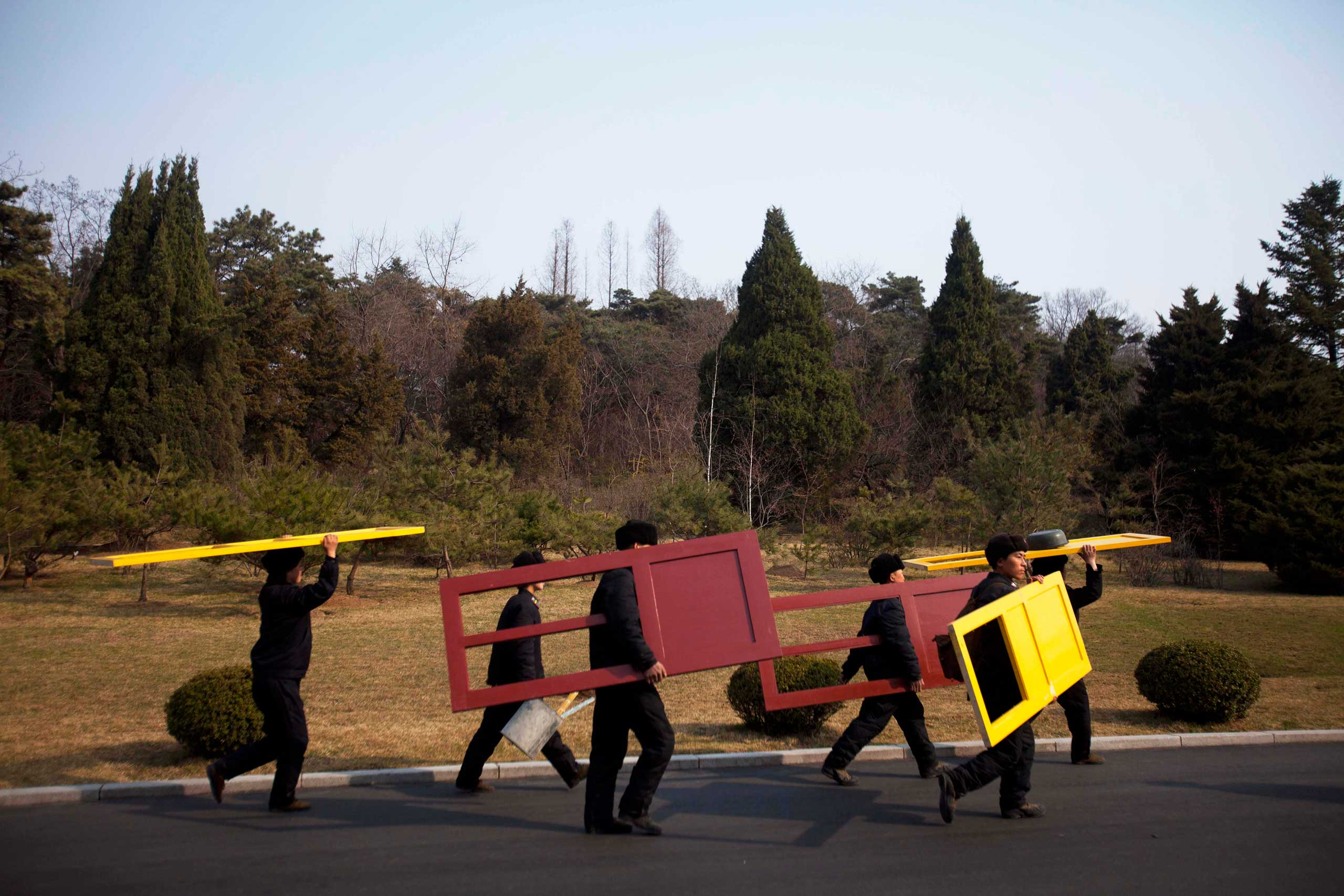 April 13, 2011. Workers carry painted doors along a road in Mangyongdae, North Korea.