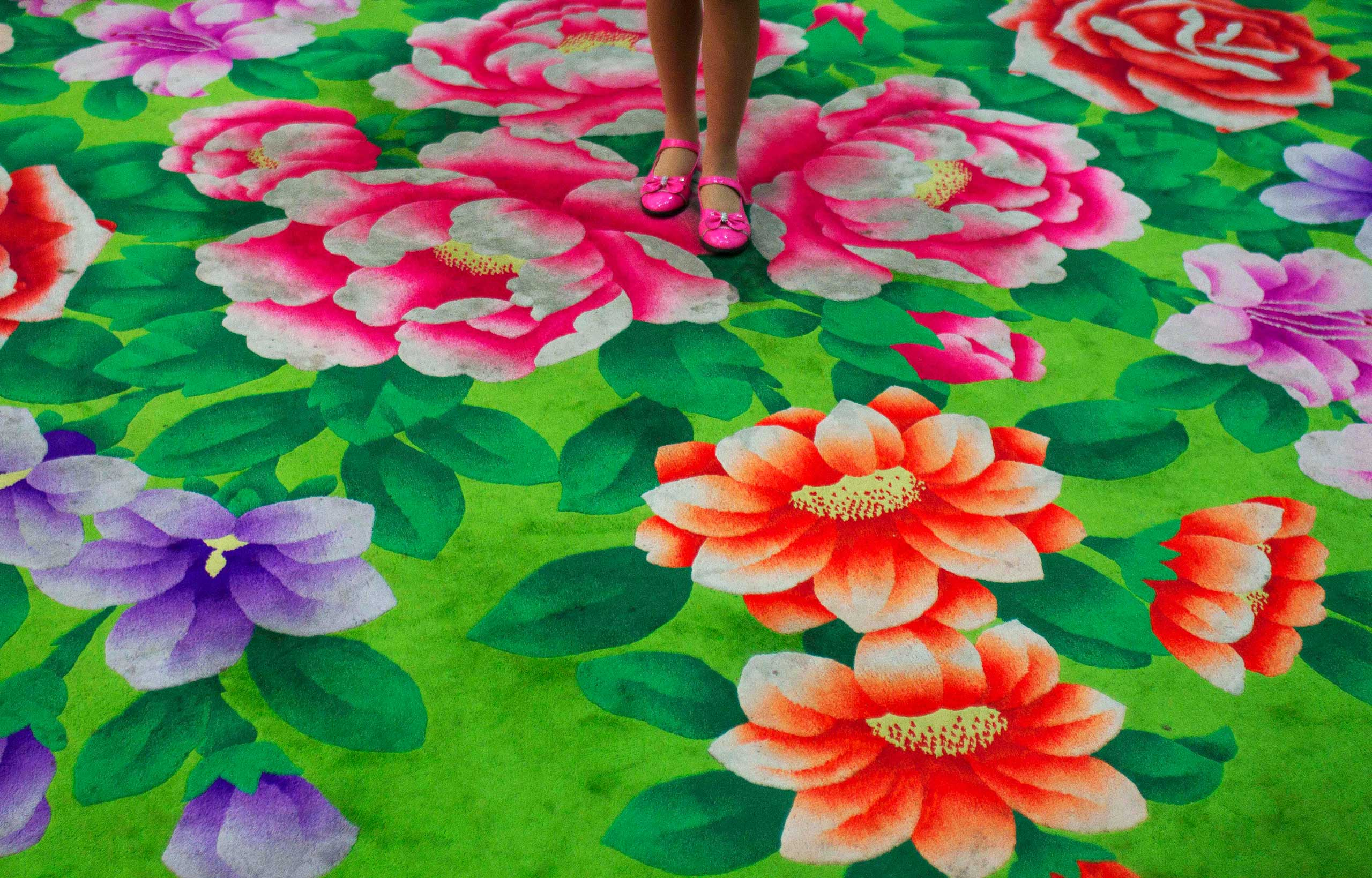April 14, 2011. A young girl stands on floral-print carpet inside the Pyongyang Children's Palace in Pyongyang.