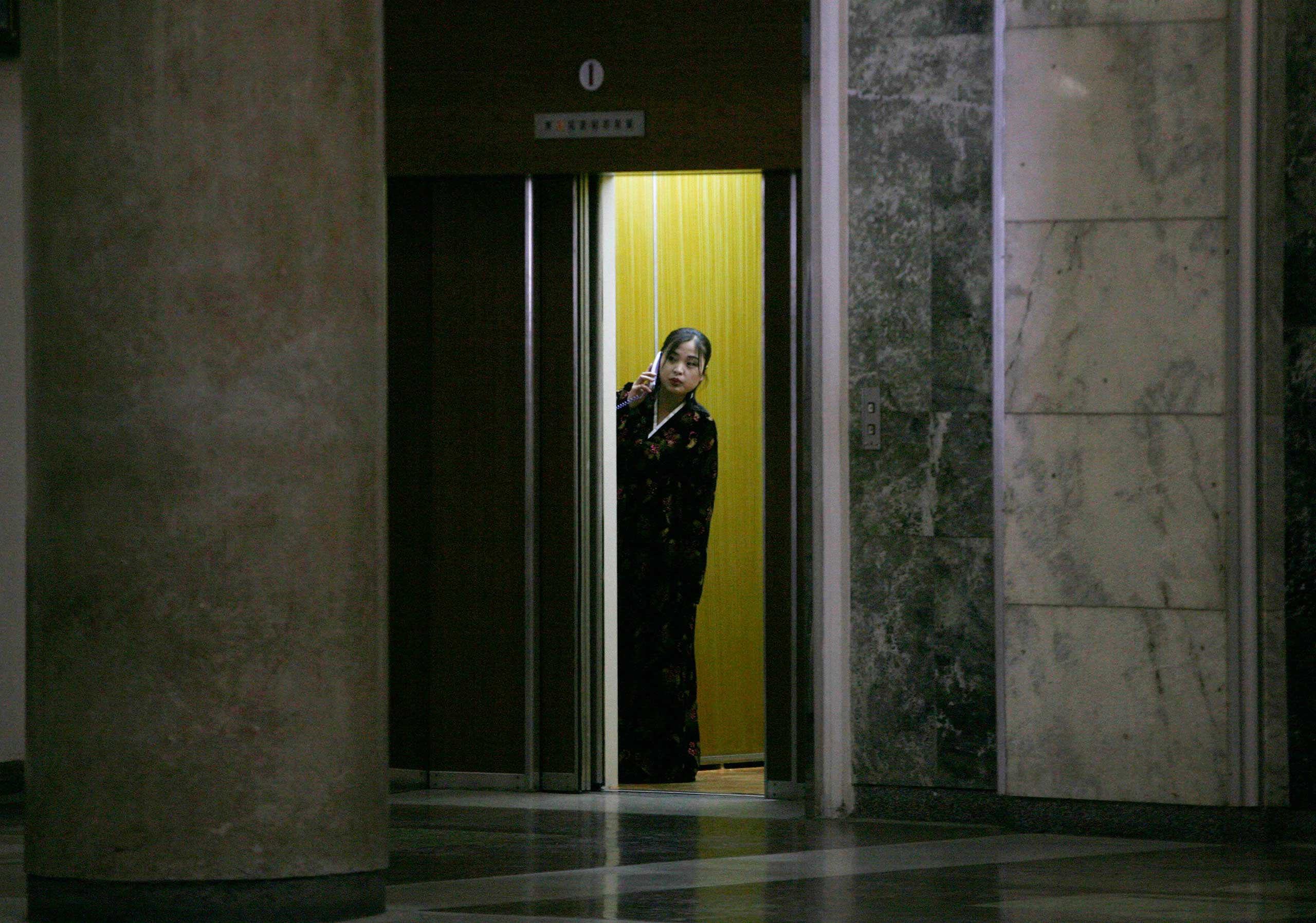Feb. 26, 2008. A North Korean woman peers out of an elevator while speaking on an in-house phone at a library in Pyongyang.