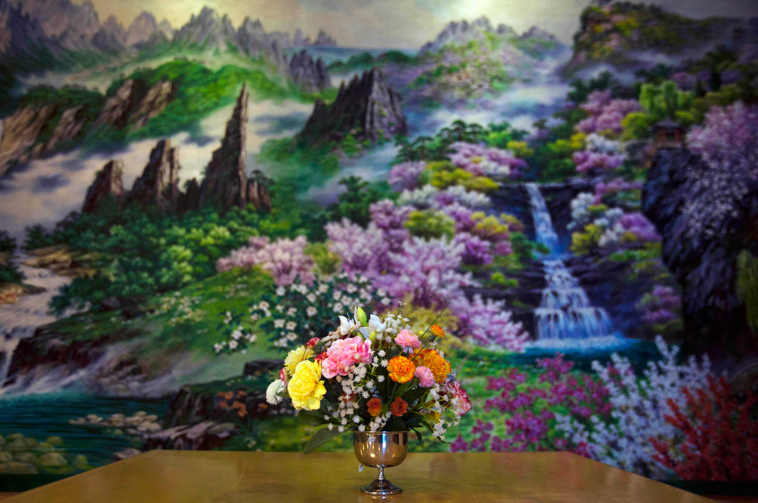 Feb. 12, 2012. A bouquet of flowers sits on a table in front of a painted mural on the wall of a restaurant in Pyongyang.
