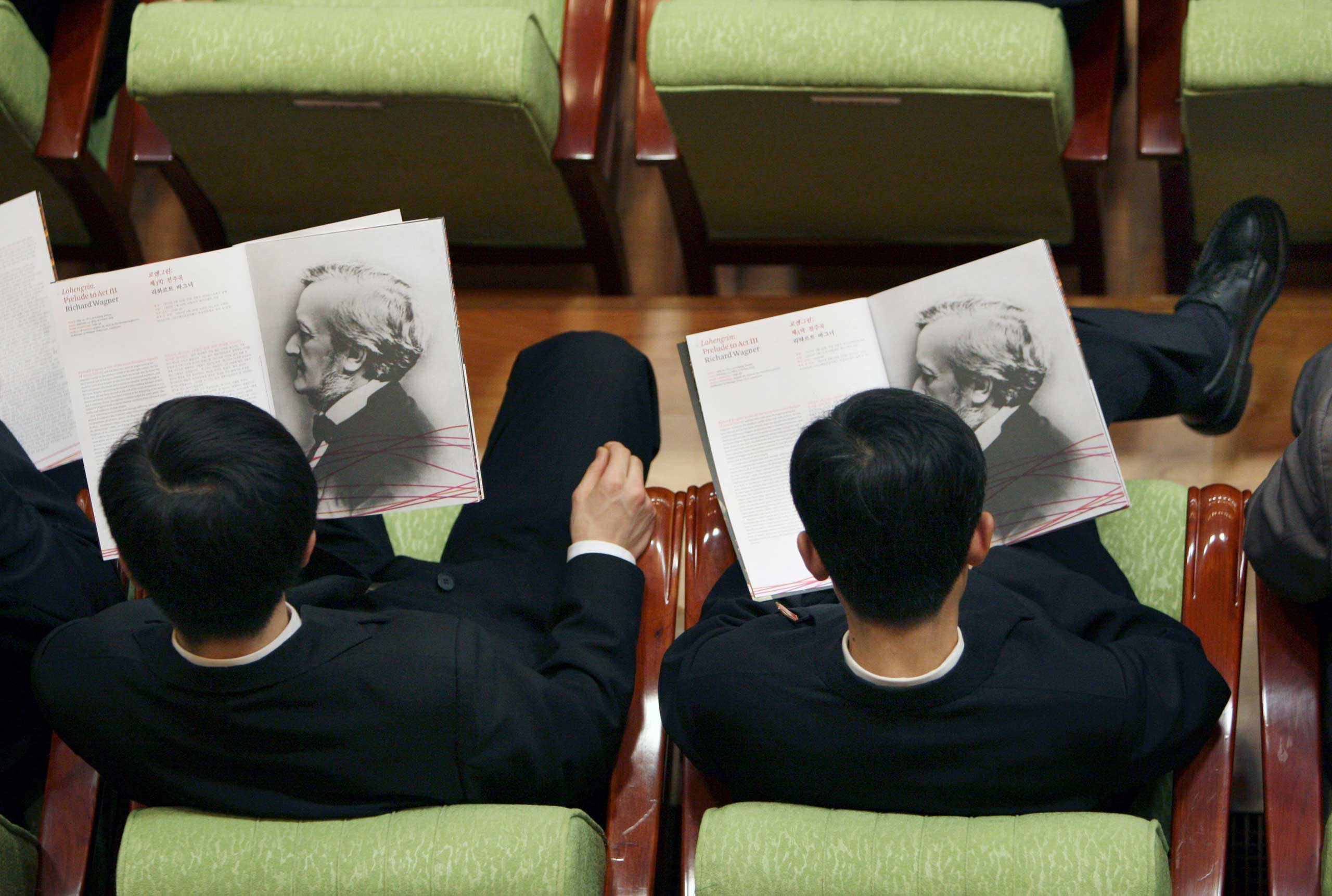 Feb. 26, 2008. North Koreans look through the performance program before the start of a concert by the New York Philharmonic in Pyongyang.
