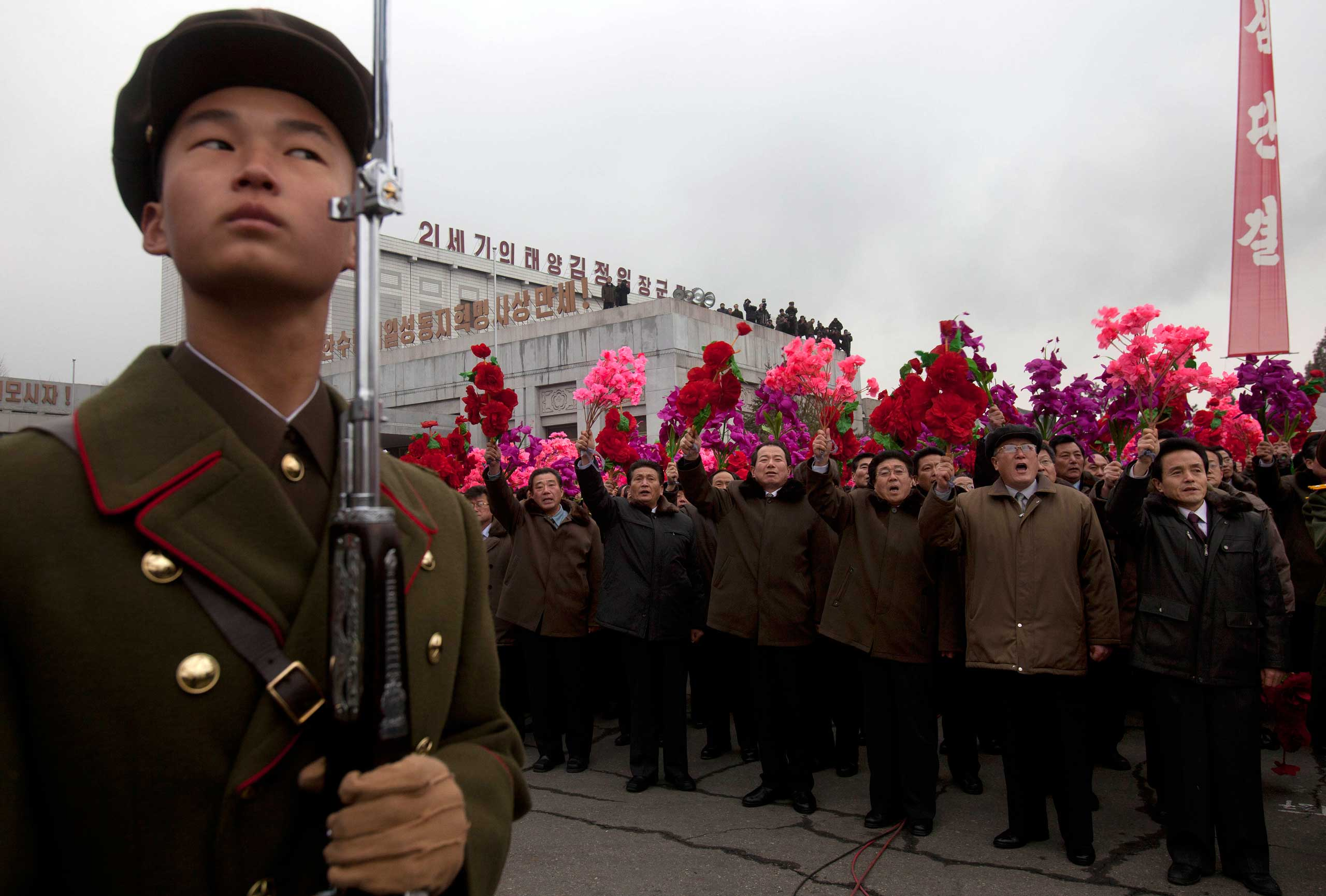 Feb. 14, 2012. A North Korean stands at attention as others cheer during the unveiling of a new bronze statue depicting the late leader Kim Jong-Il and his father Kim Il-Sung at Mansudae Art Studio in Pyongyang.