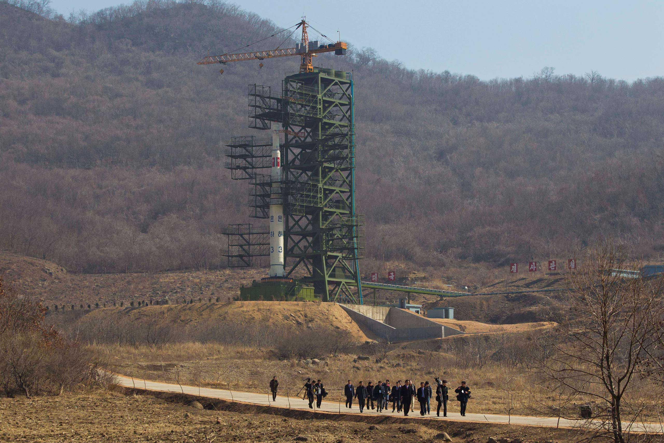 April 8, 2012. A group of journalists walk down a road in front of North Korea's Unha-3 rocket, slated for liftoff at Sohae Satellite Station.