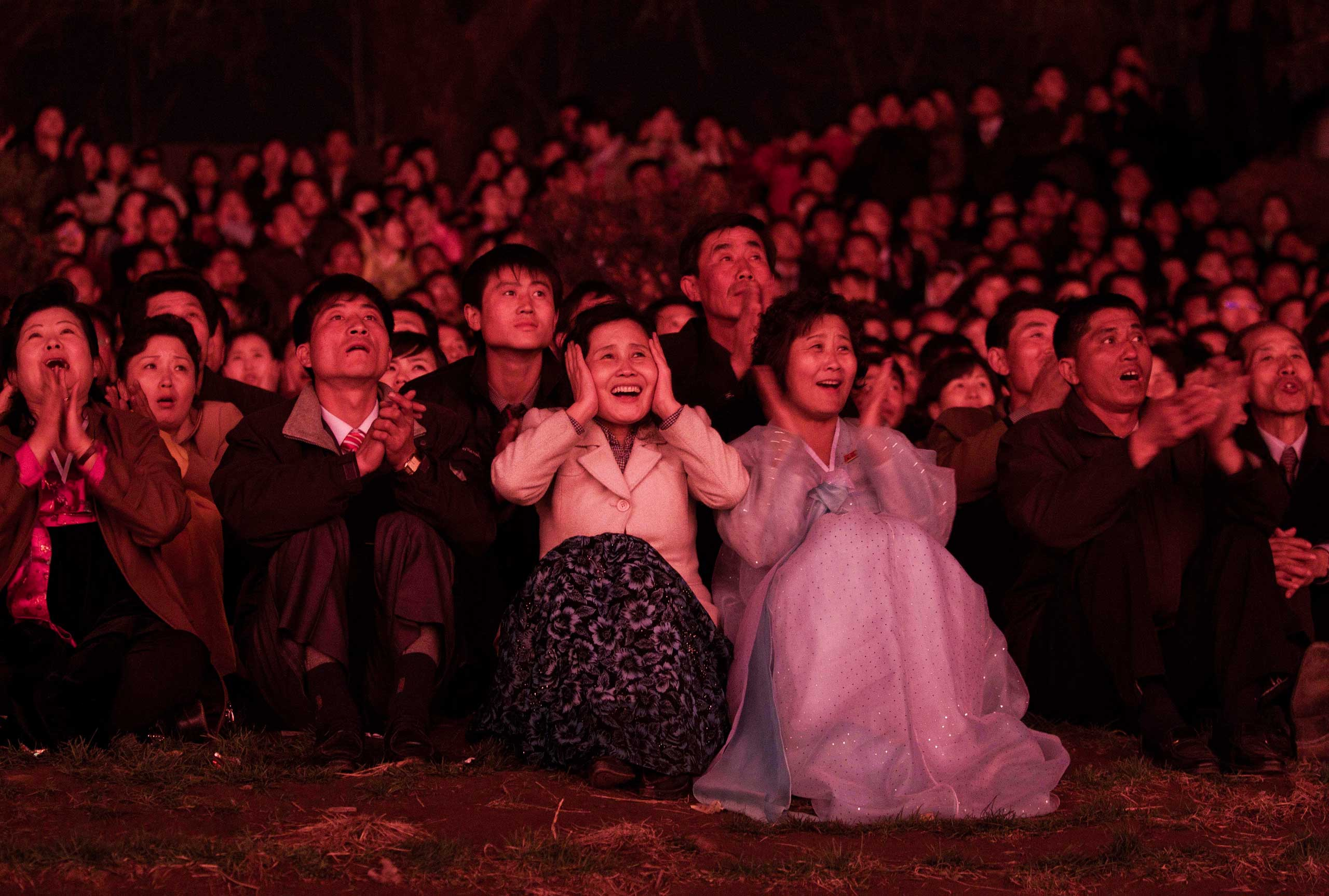 April 15, 2012. North Koreans, lit with red light, look on with delight as they watch a fireworks display along the Taedong River in Pyongyang to celebrate 100 years since the birth of the late North Korean founder Kim Il-Sung.