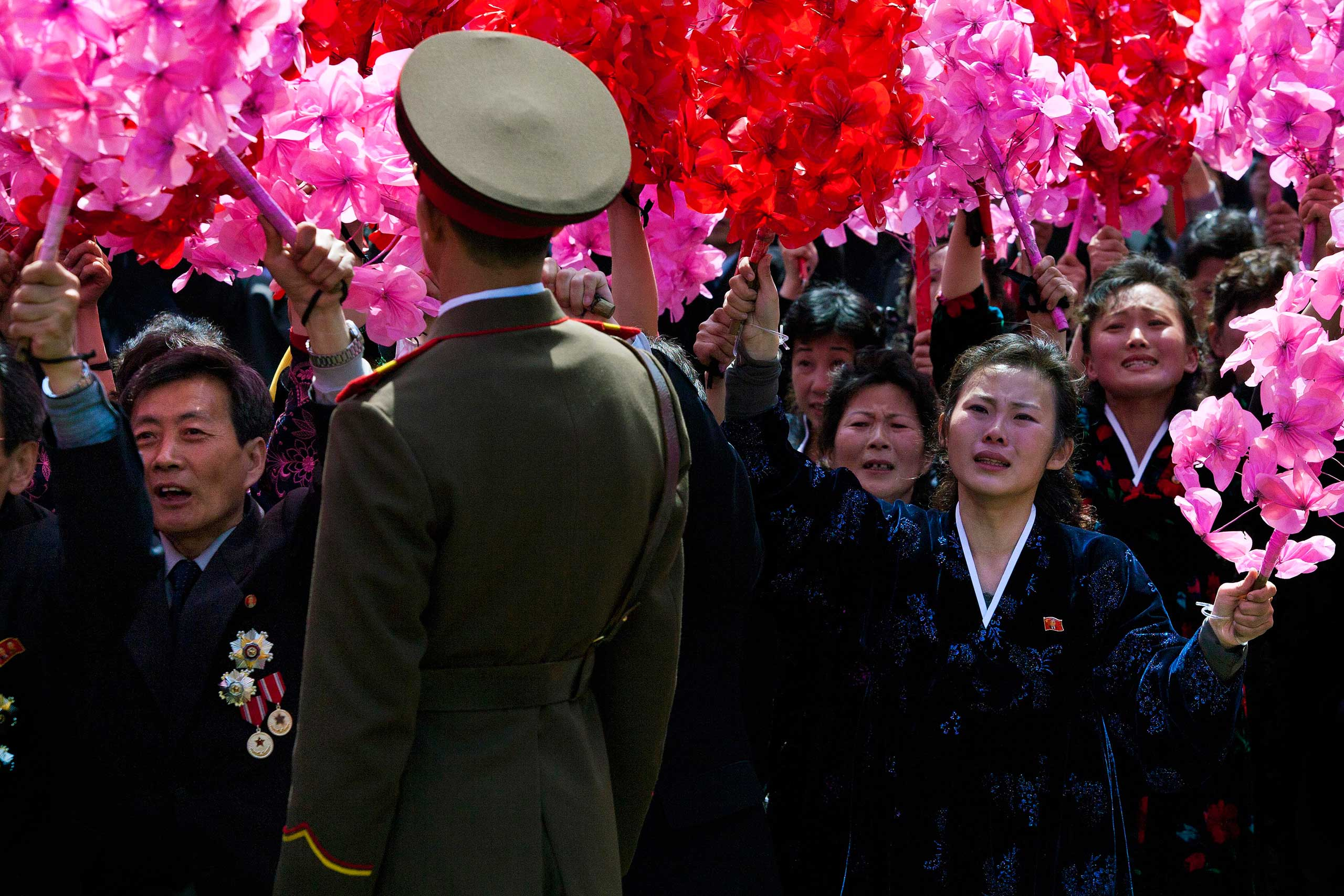 April 15, 2012. North Korean civilians, some weeping, wave flowers as they look up at North Korean leader Kim Jong-Un, unseen, at the end of a mass military parade in Pyongyang's Kim Il Sung Square to celebrate 100 years since the birth of the late North Korean founder Kim Il-Sung.
