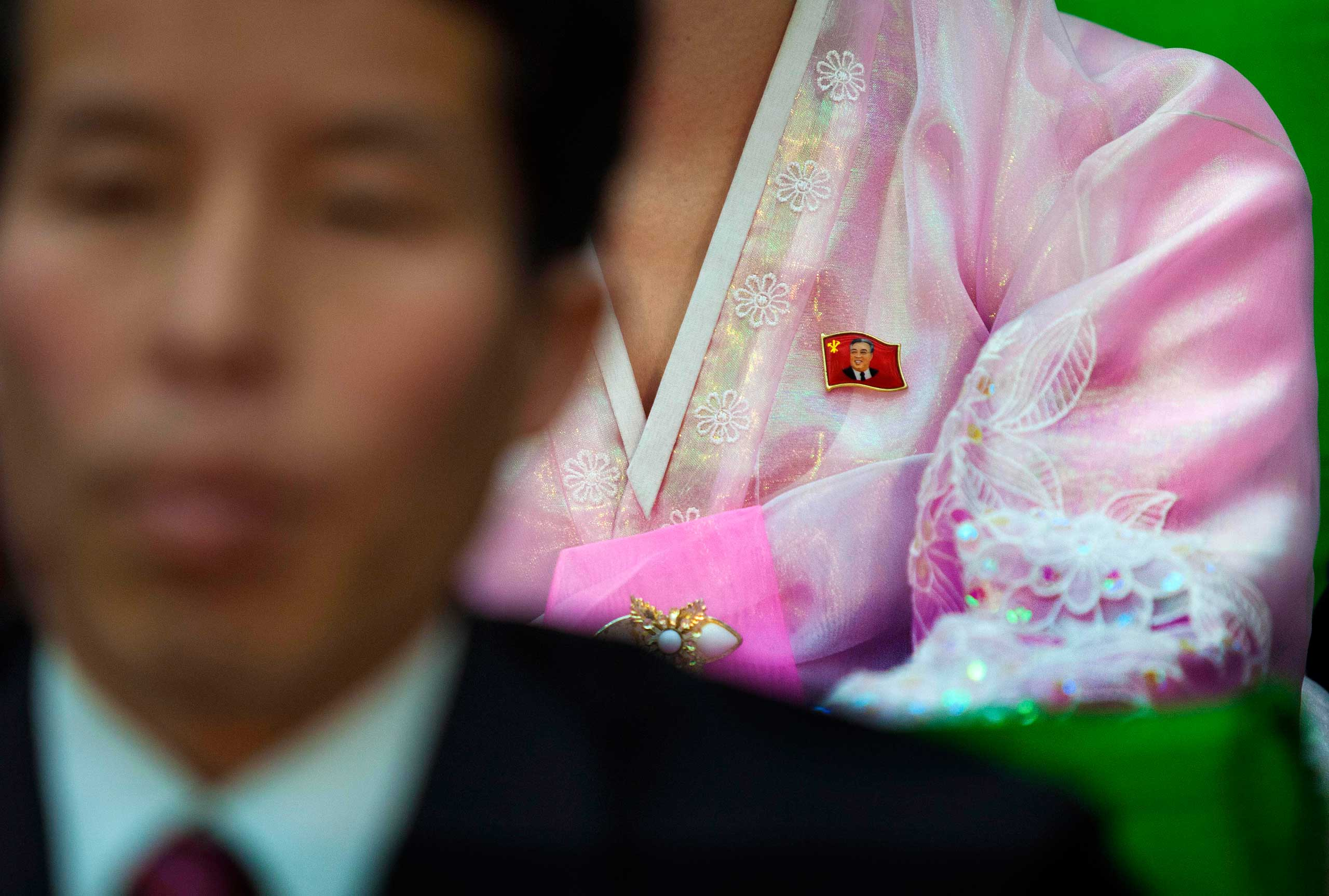 "April 12, 2012. A North Korean woman with a pin of the late leader Kim Il Sung attached to her dress sits with fellow audience members at the ""World Congress on the Juche Idea"" in Pyongyang."