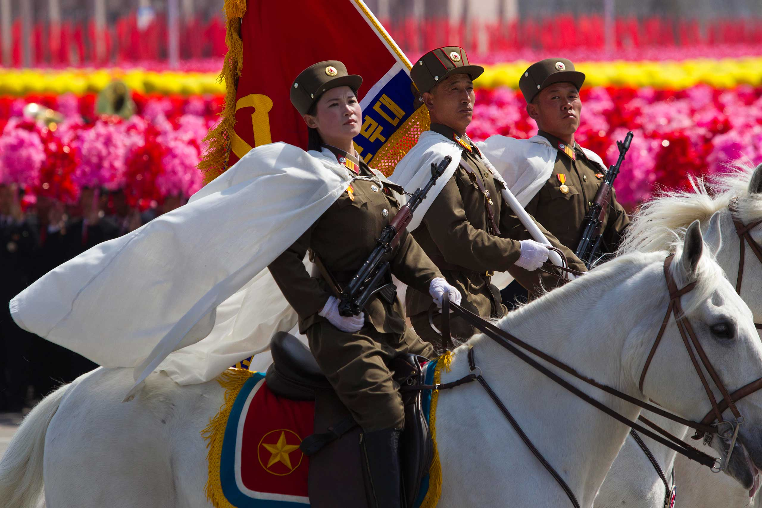 April 15, 2012. North Korean soldiers ride by on horses in front of flower waving civilians during a mass military parade in Pyongyang's Kim Il-Sung Square to celebrate 100 years since the birth of the late North Korean founder Kim Il-Sung.