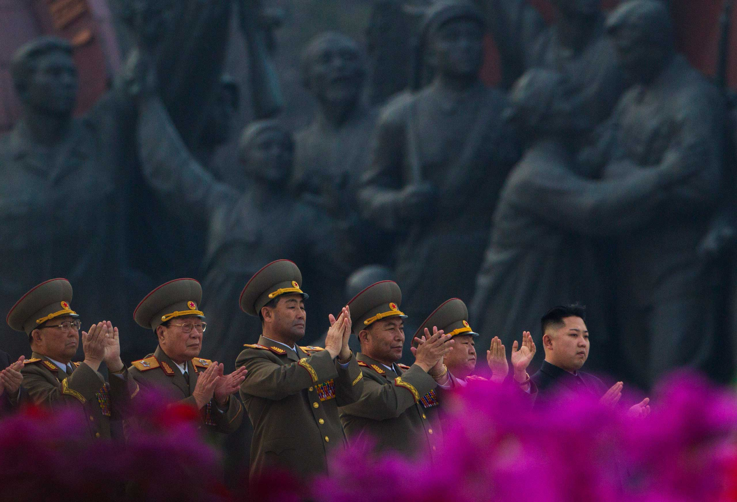 April 13, 2012. North Korean leader Kim Jong Un, far right, applauds with senior military officials as citizens wave flowers at an unveiling ceremony for statues of the late leaders Kim Il-Sung and Kim Jong-Il in Pyongyang.