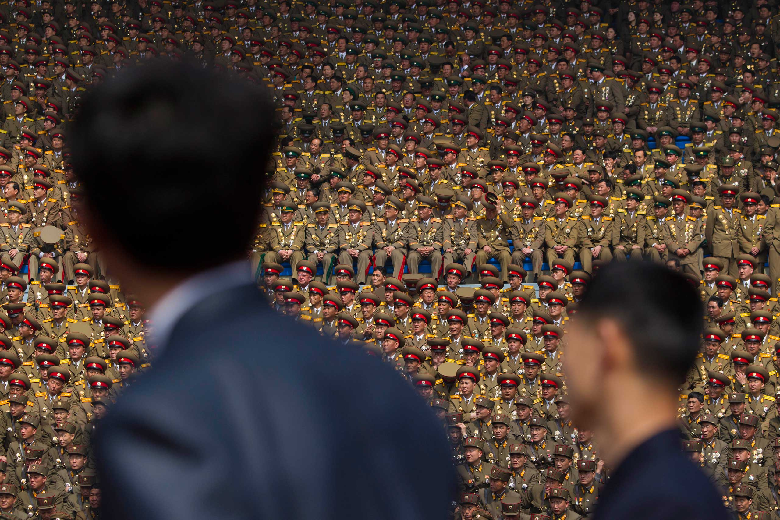 April 15, 2012. Two North Korean officials look up at a crowd of military members seated in a stadium in Pyongyang during a mass meeting called by the Central Committee of North Korea's ruling party.