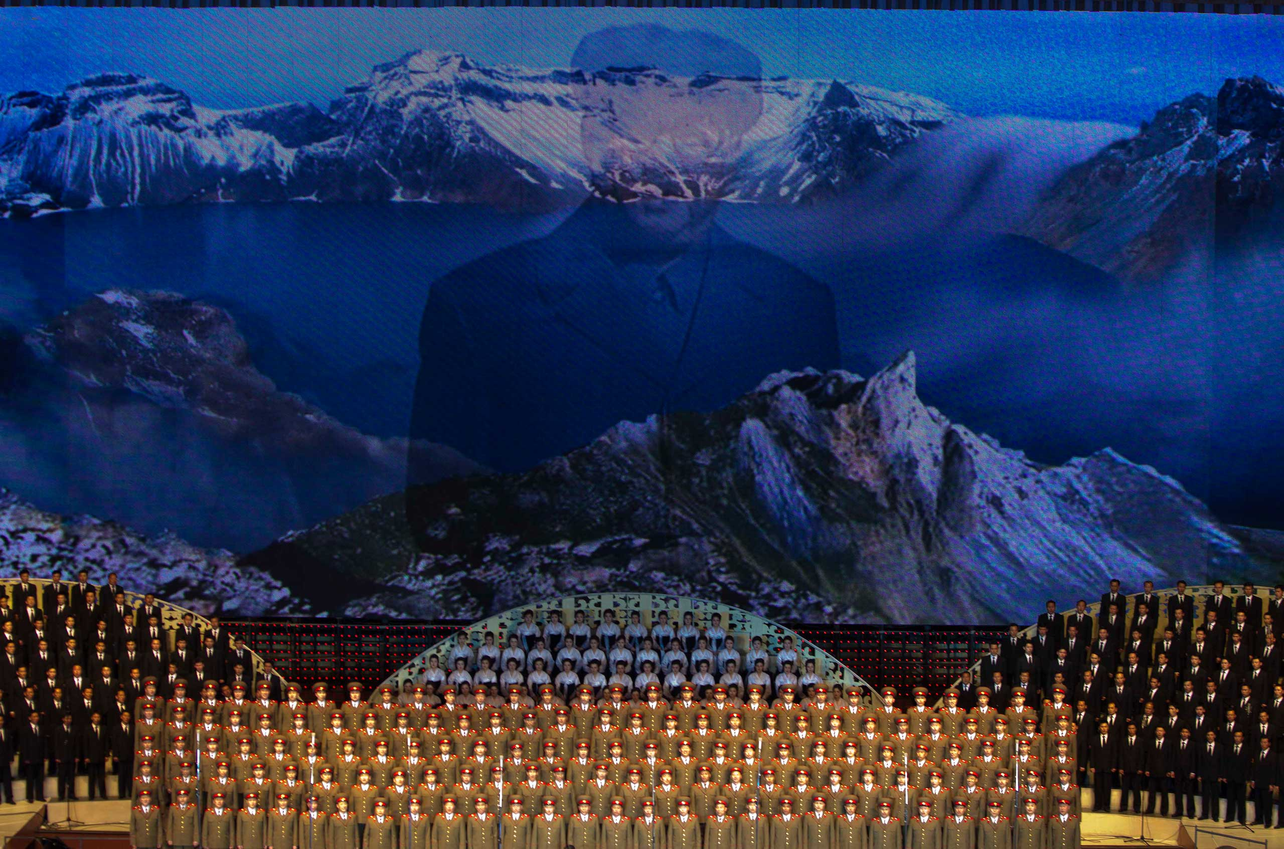 April 16, 2012. Images of the late North Korean leader Kim Il-Sung and Mt. Paektu appear on a screen behind a choir during a concert in Pyongyang.