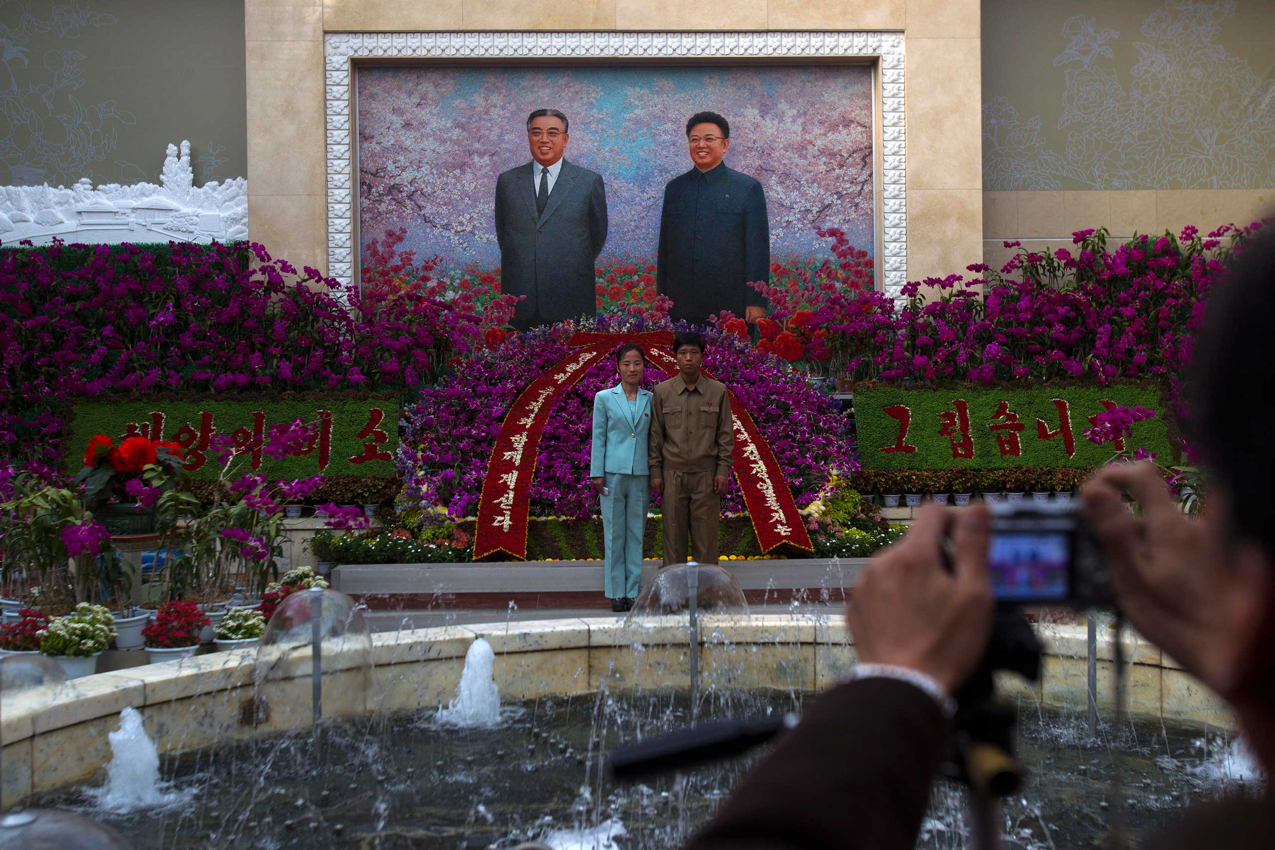 "April 17, 2012. A man and a boy pose for a picture in front of portraits of the late leaders Kim Il-Sung and Kim Jong-Il at a festival for the ""Kimilsungia"" flower to mark 100 years since the birth of North Korea's late leader in Pyongyang."
