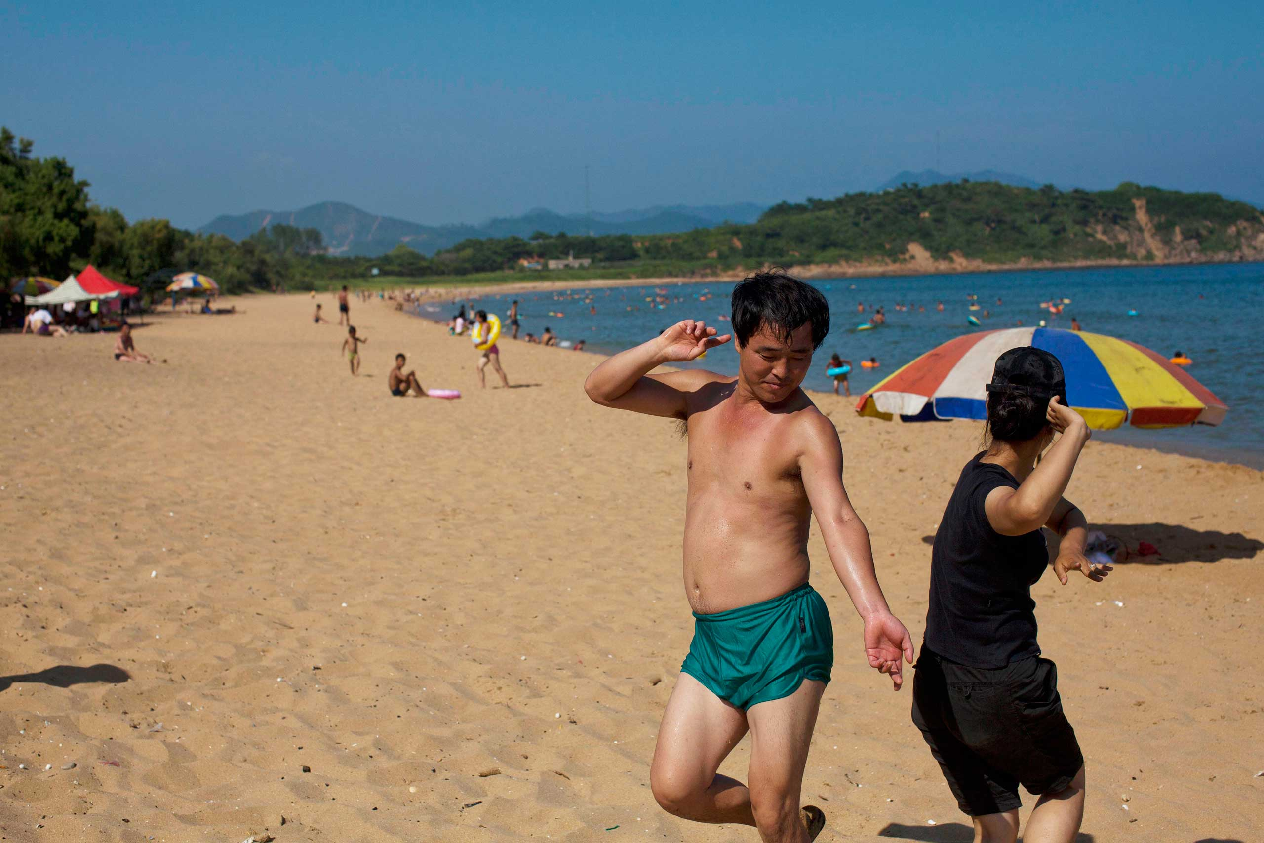 Aug. 11, 2012. Two people dance at Majon beach near Hamhung, North Korea.