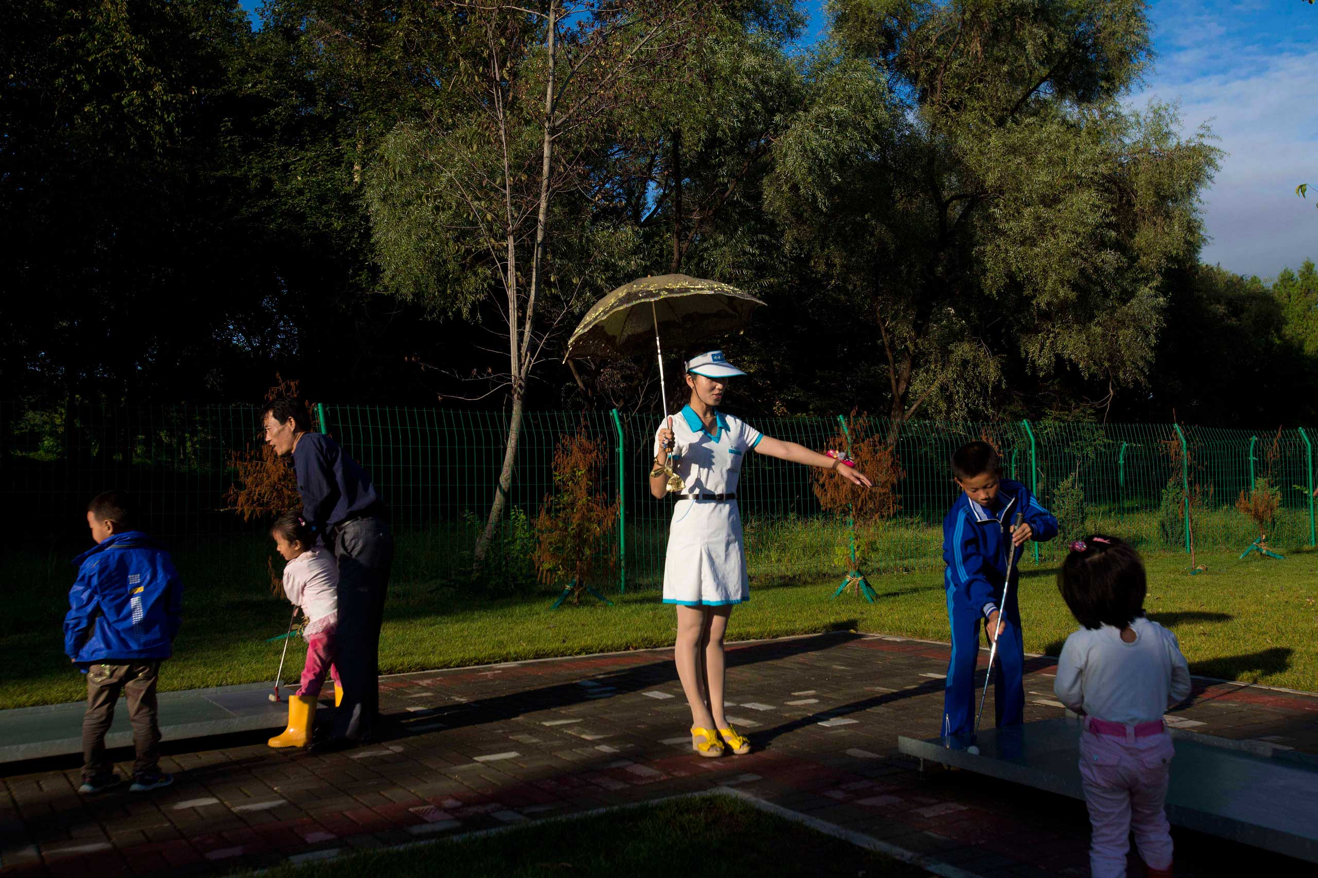 Sept. 8, 2012. A North Korean woman working at a miniature golf facility give guidance to young players in Pyongyang, North Korea.