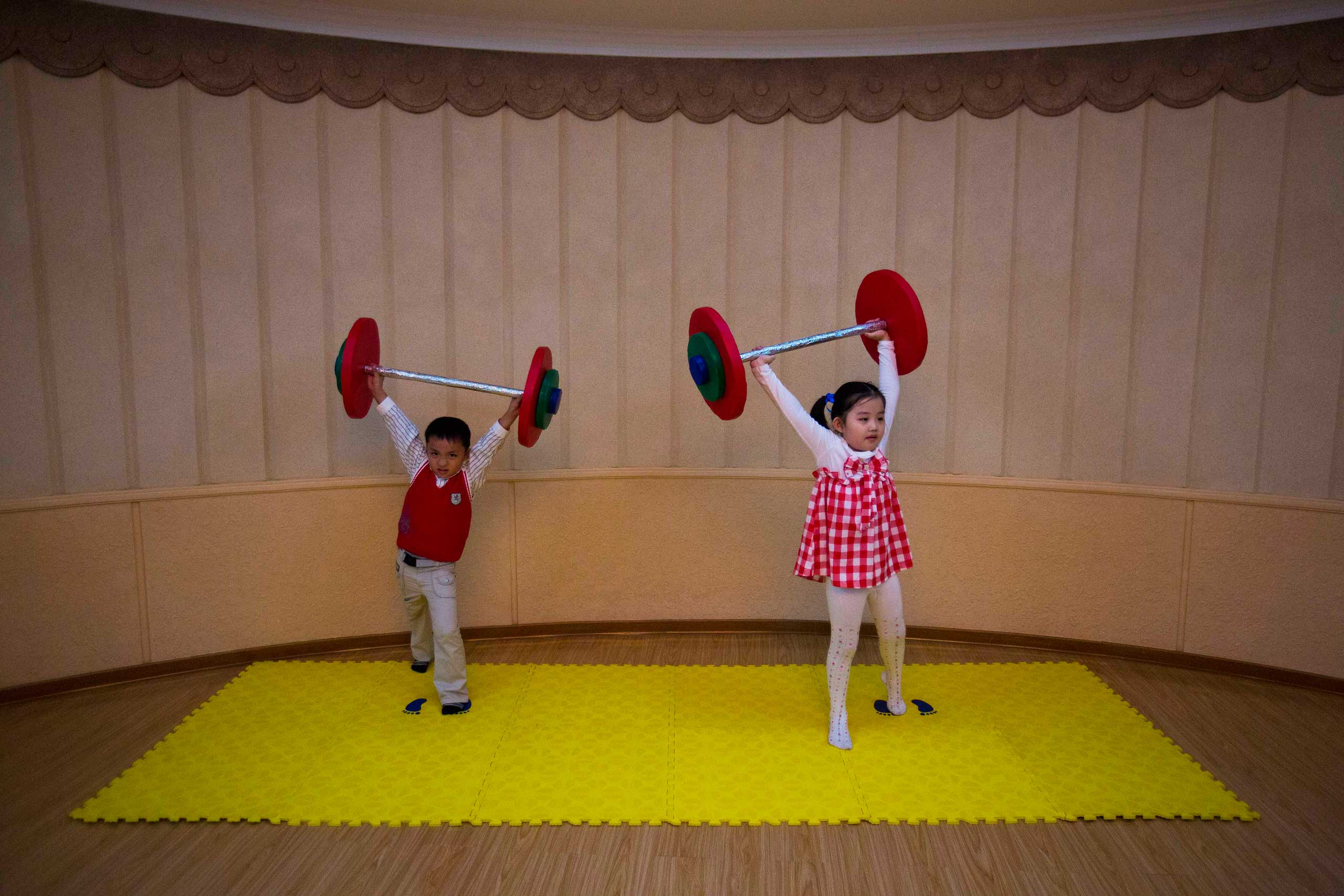 Sept. 13, 2012. North Korean children lift toy barbells during play time at a school for the performing arts in Pyongyang, North Korea.