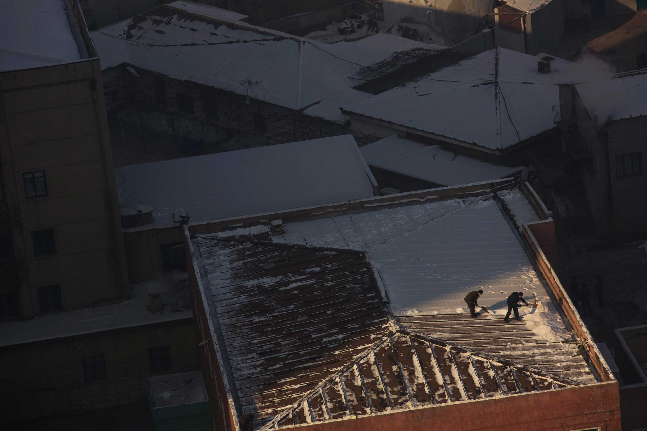 Jan. 10, 2013. North Korean men shovel snow from the roof of a building in Pyongyang, North Korea.