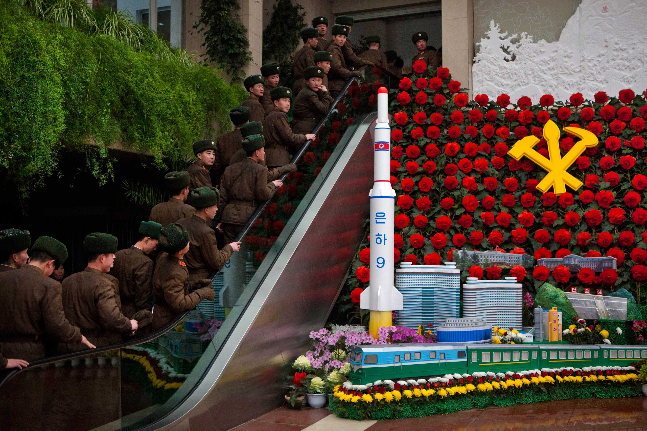 Feb. 17, 2013. North Korean soldiers ride an escalator past a model of their country's Unha Rocket as they enter an exhibition in Pyongyang, North Korea.
