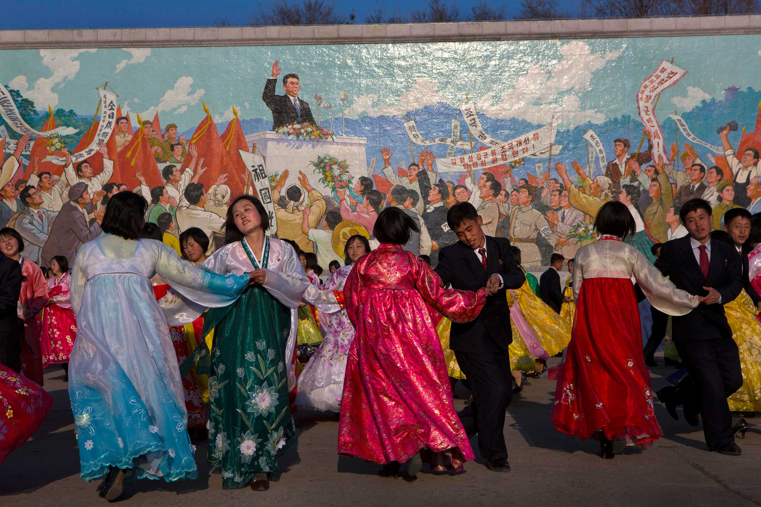 April 11, 2013. North Koreans dance together beneath a mosaic painting of the late leader Kim Il Sung during a mass folk dancing gathering in Pyongyang to mark the anniversary of the first of many titles of power given to leader Kim Jong Un after the death of his father Kim Jong Il.