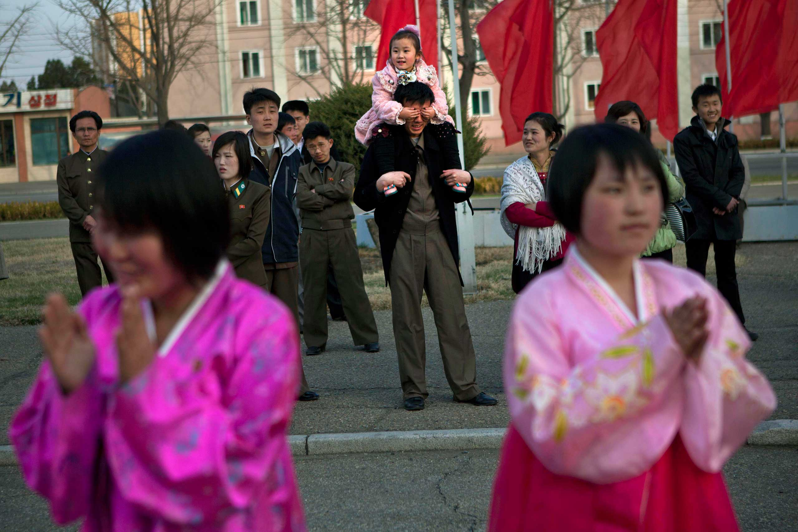 April 15, 2013. A North Korean child covers the eyes of her father as she sits on his shoulders watching mass folk dancing in front of Pyongyang Indoor Stadium in Pyongyang, North Korea.