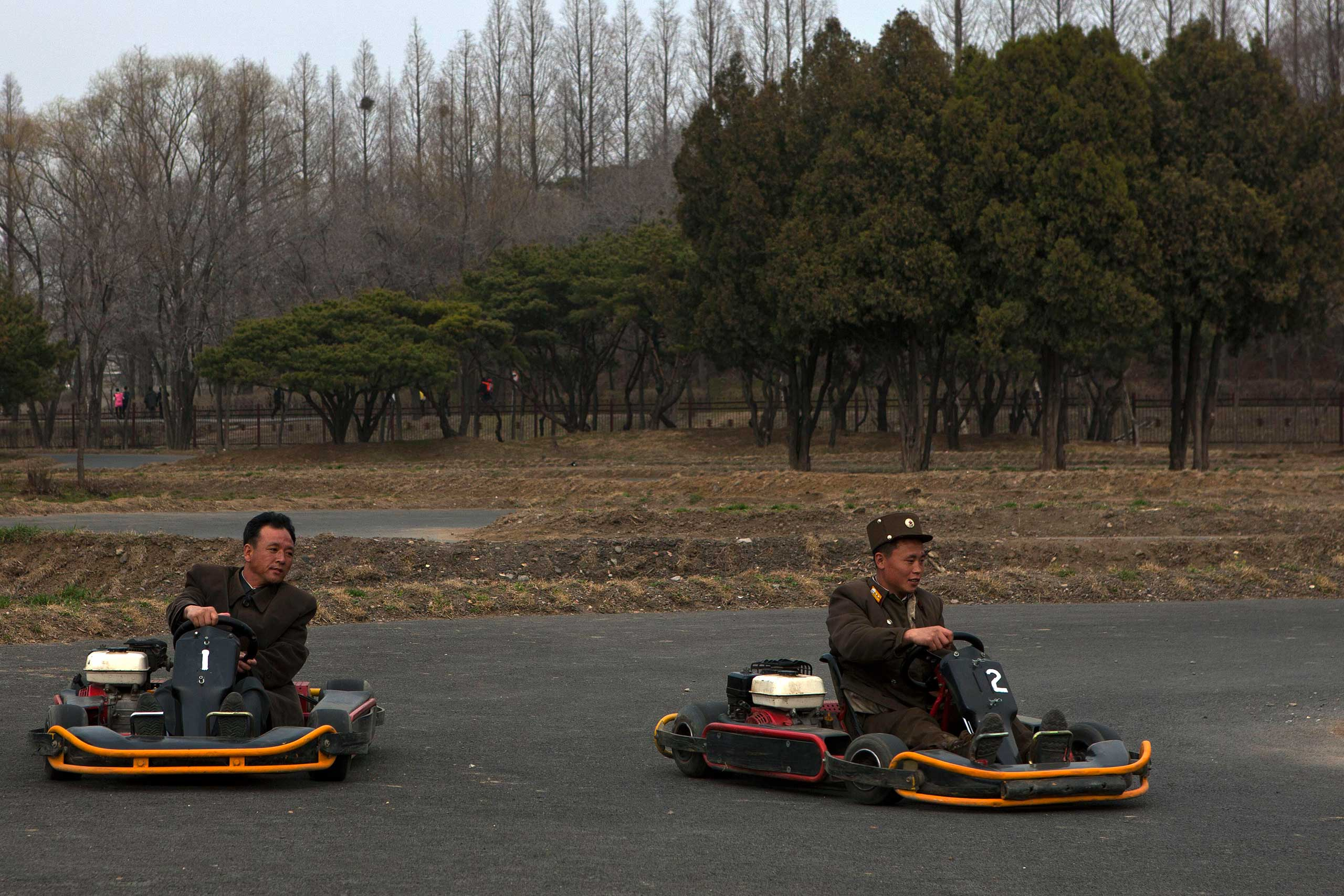April 16, 2013. A North Korean soldier races another man on a go cart track at the Fun Fair in Pyongyang, North Korea.
