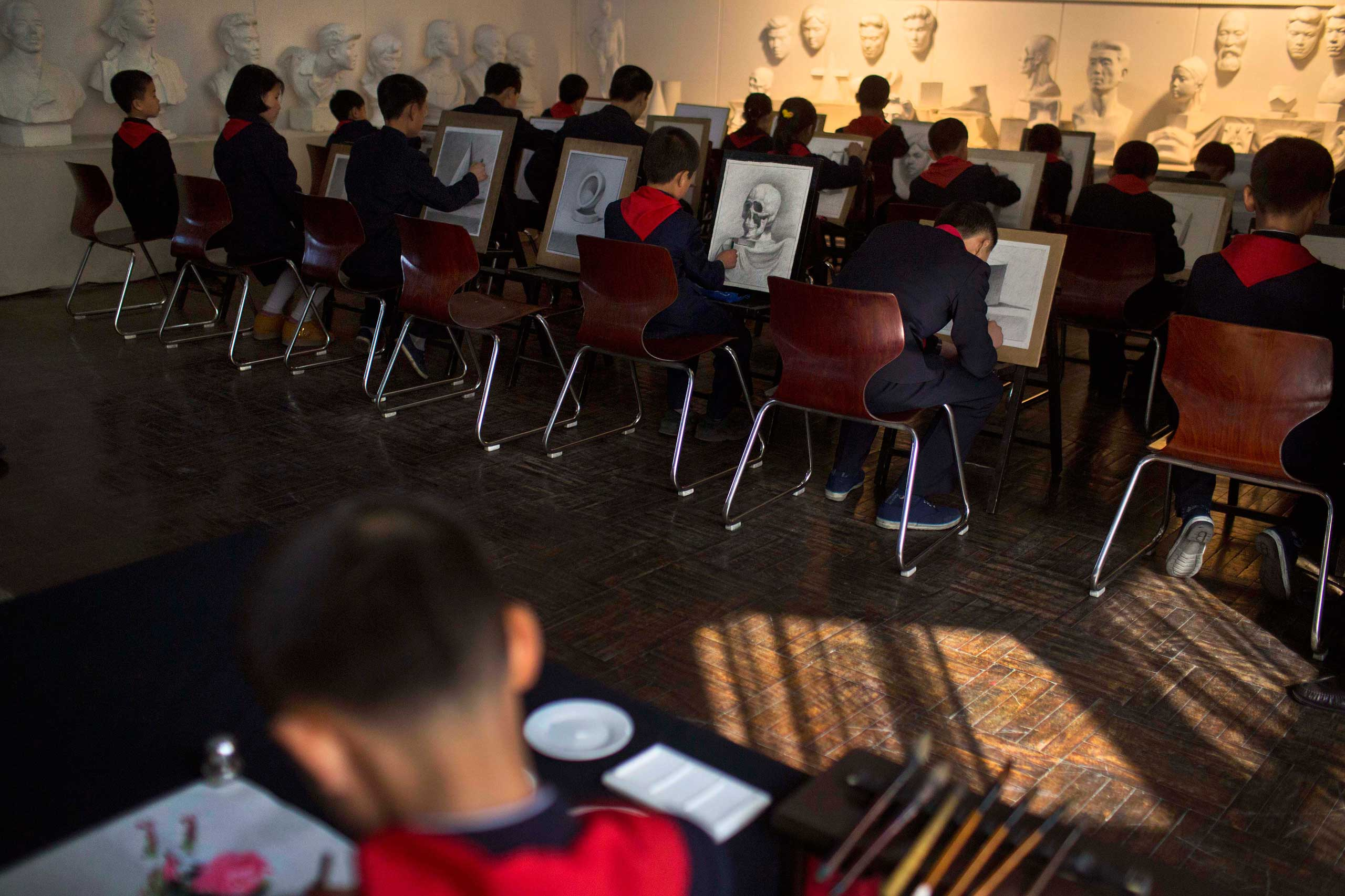 April 18, 2013. North Korean children work at easels during a drawing class at Mangyongdae Children's Palace in Pyongyang, North Korea.