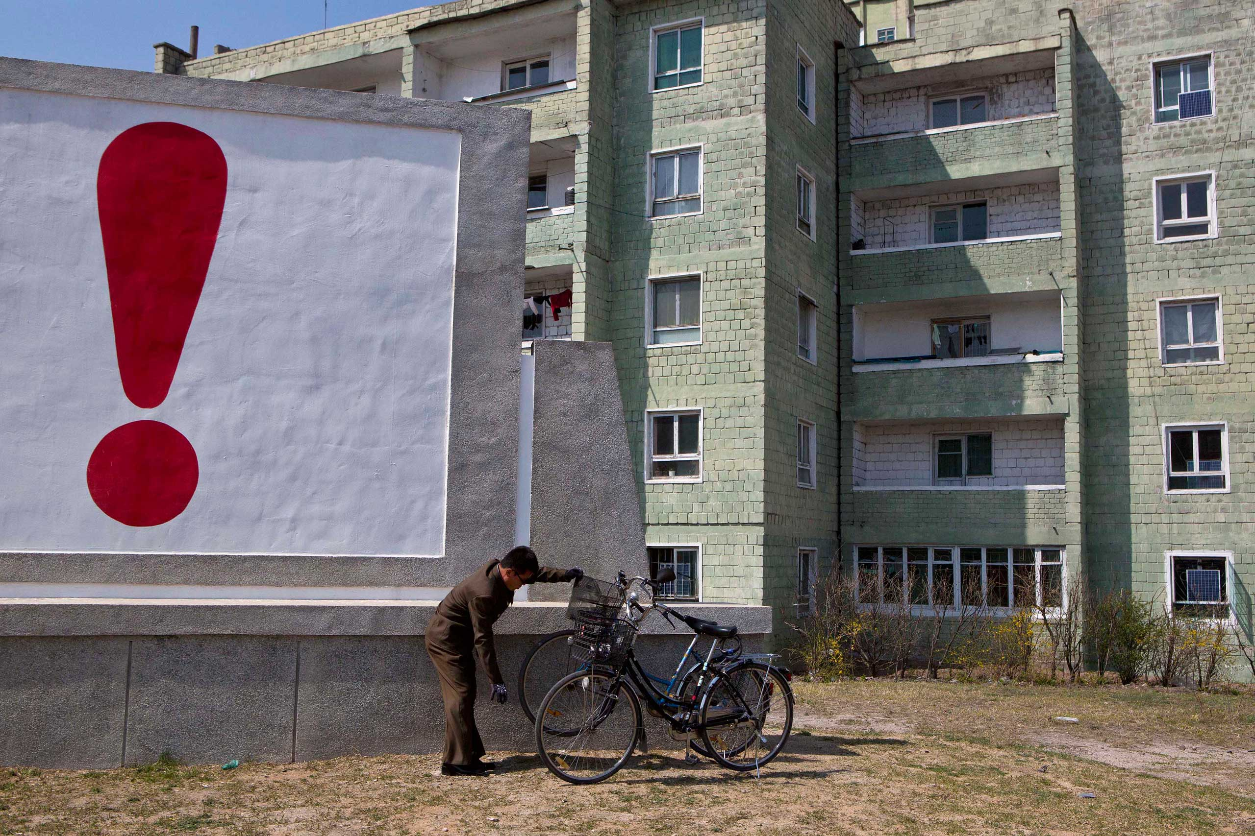 April 24, 2013. A North Korean man checks his bicycle next to a painted exclamation point on a propaganda billboard in Kaesong, North Korea.