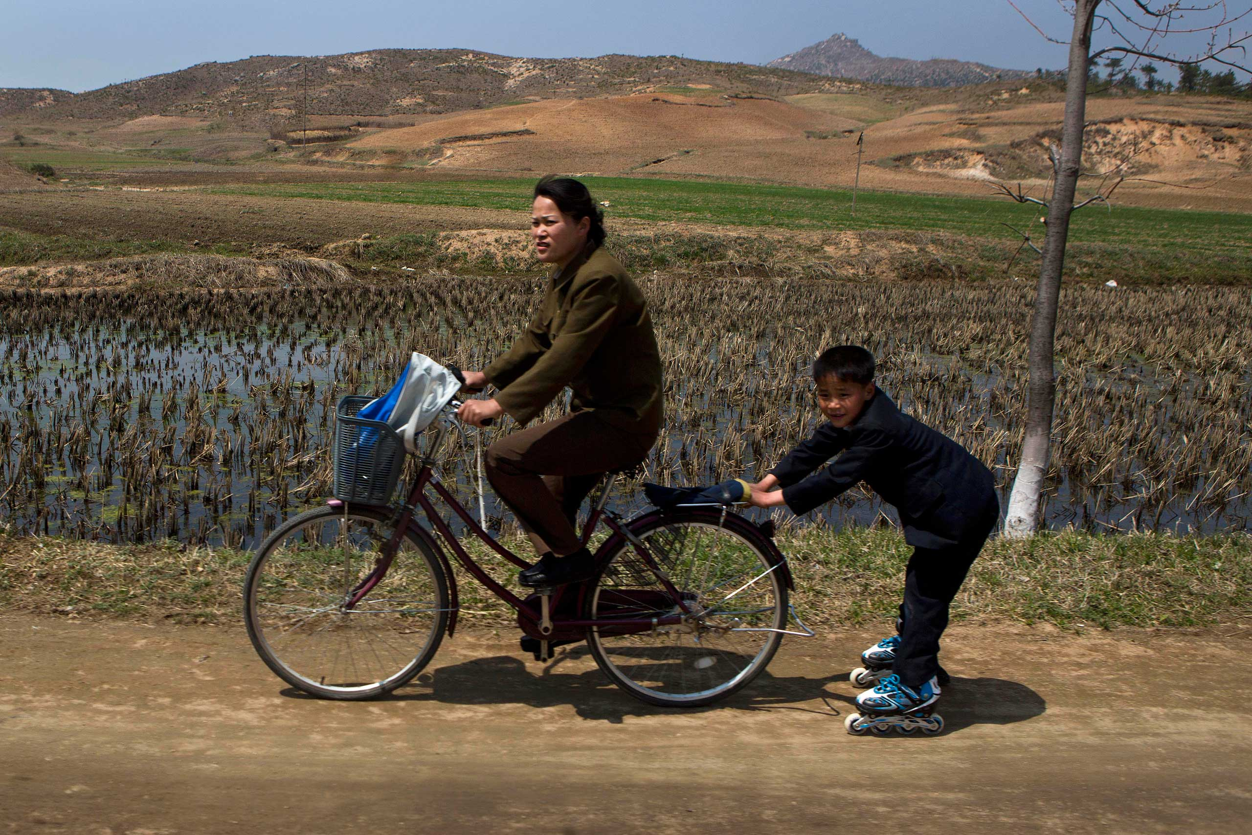 April 24, 2013. A North Korean boy on rollerblades is pulled by a woman on a bicycle on a road south of Kaesong, North Korea and north of the demilitarized zone which separates the two Koreas.