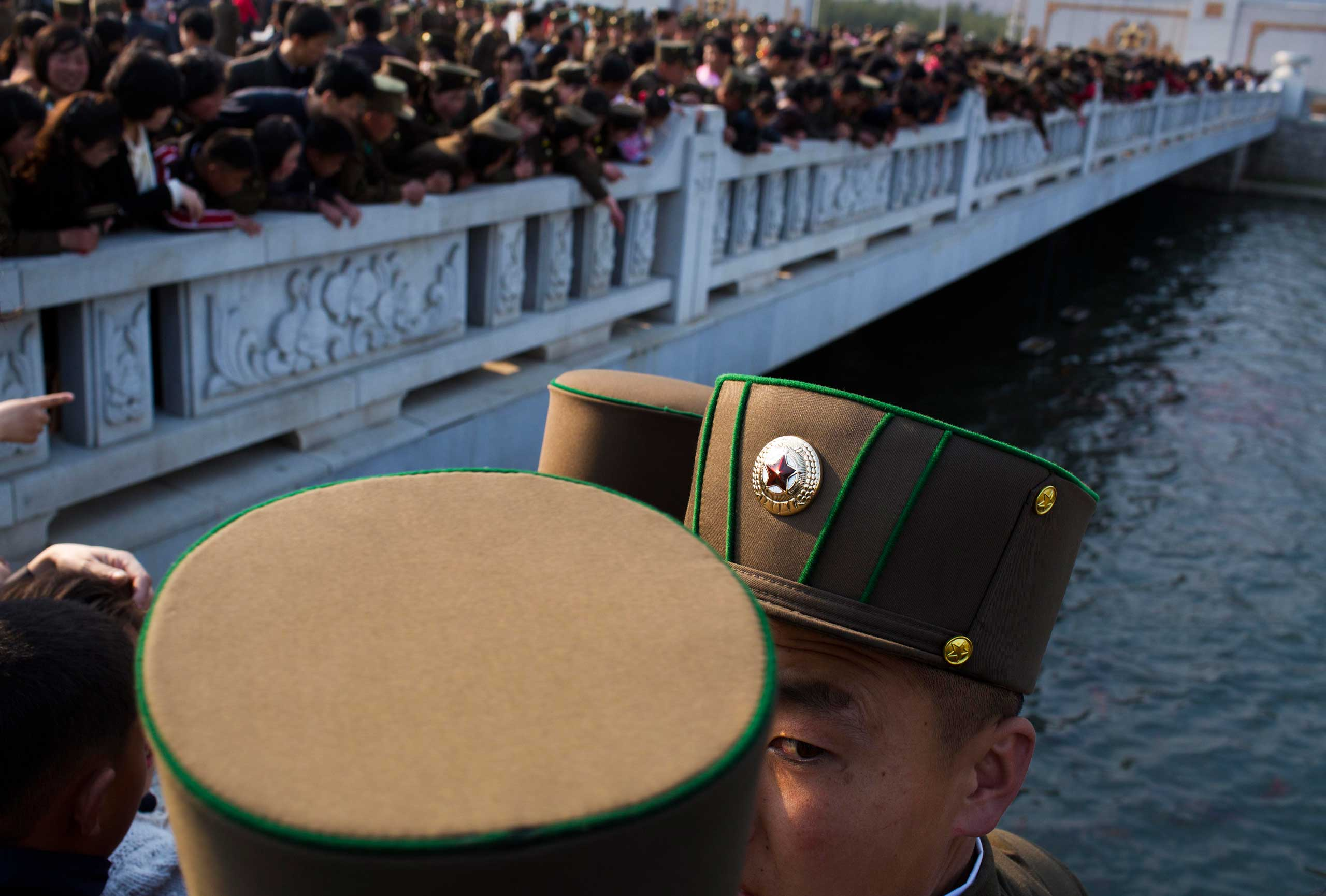 April 25, 2013. North Korean soldiers and civilians stand on a foot bridge to look at goldfish in a moat as they tour the grounds of Kumsusan Palace of the Sun, the mausoleum where the bodies of the late leaders Kim Il Sung and Kim Jong Il lie embalmed, in Pyongyang, North Korea.