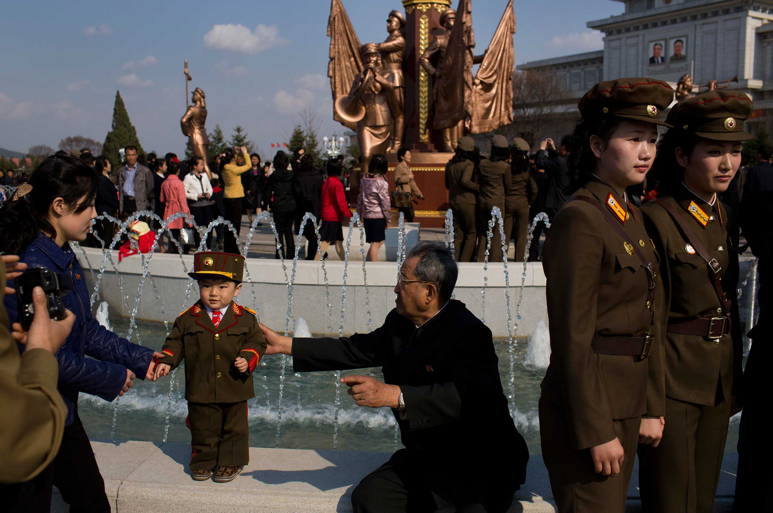 April 25, 2013. North Korean soldiers and civilians pose for souvenir photos in front of a fountain as they tour the grounds of Kumsusan Palace of the Sun, the mausoleum where the bodies of the late leaders Kim Il Sung and Kim Jong Il lie embalmed, in Pyongyang, North Korea.