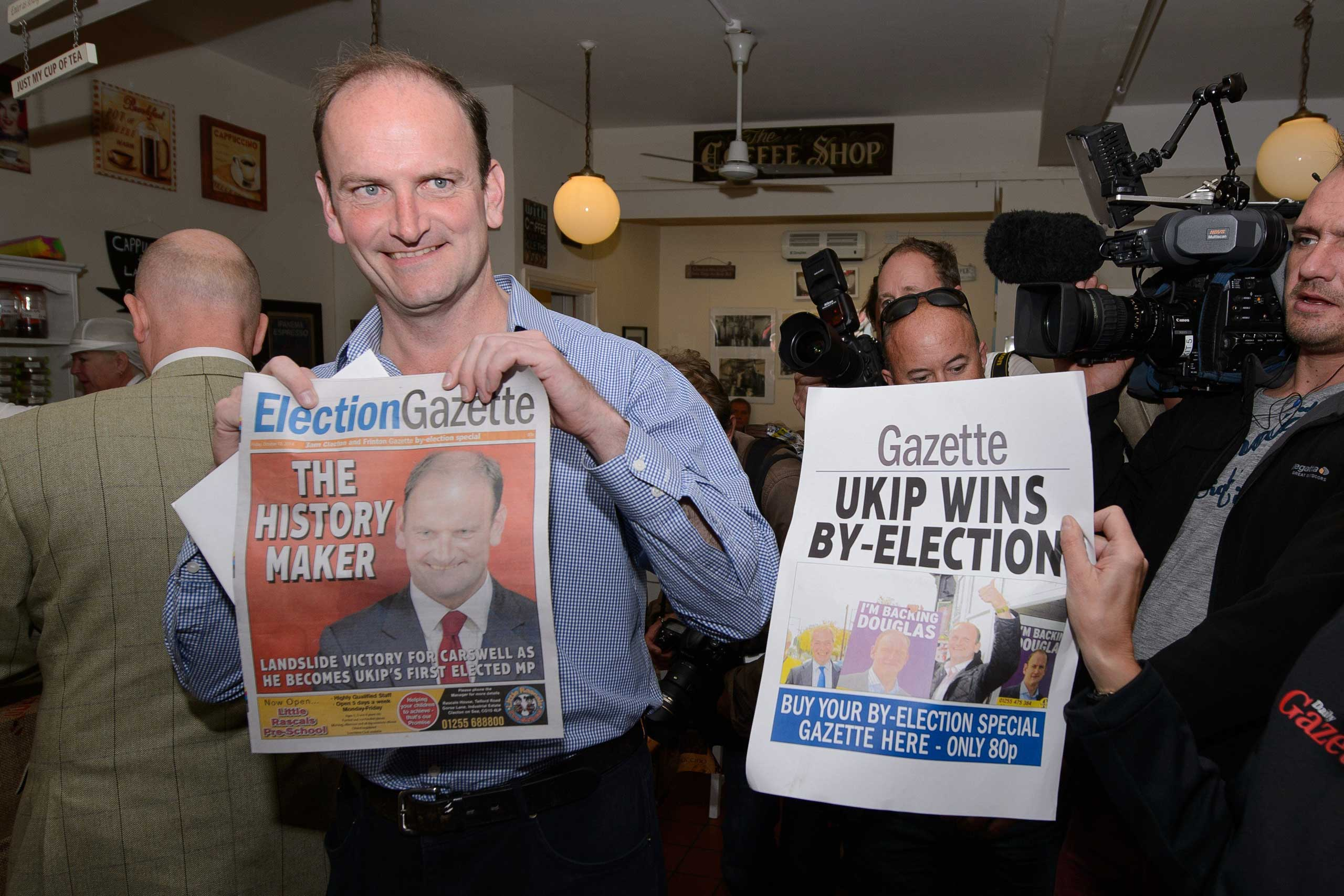 Newly-elected UK Independence Party MP Douglas Carswell poses for photographers with a copy of the local paper in Clacton-on-Sea, in eastern England, on Oct. 10, 2014.