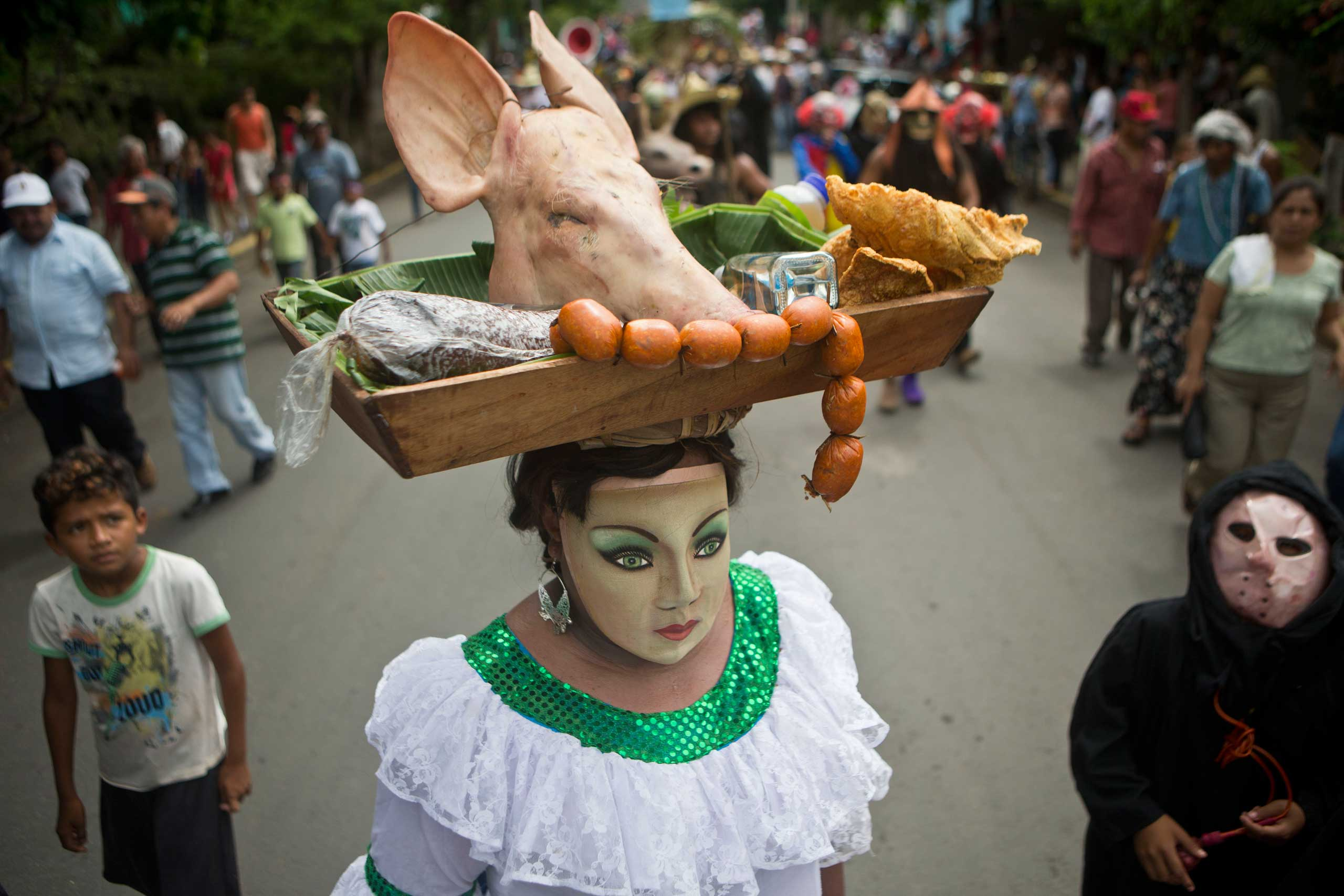 A man dressed as a woman, carries a pig's head on a platter balanced on his head during the celebration of  Torovenado,  in honor of Masaya's patron saint, San Jeronimo, in Masaya, Nicaragua, on Oct. 26, 2014.