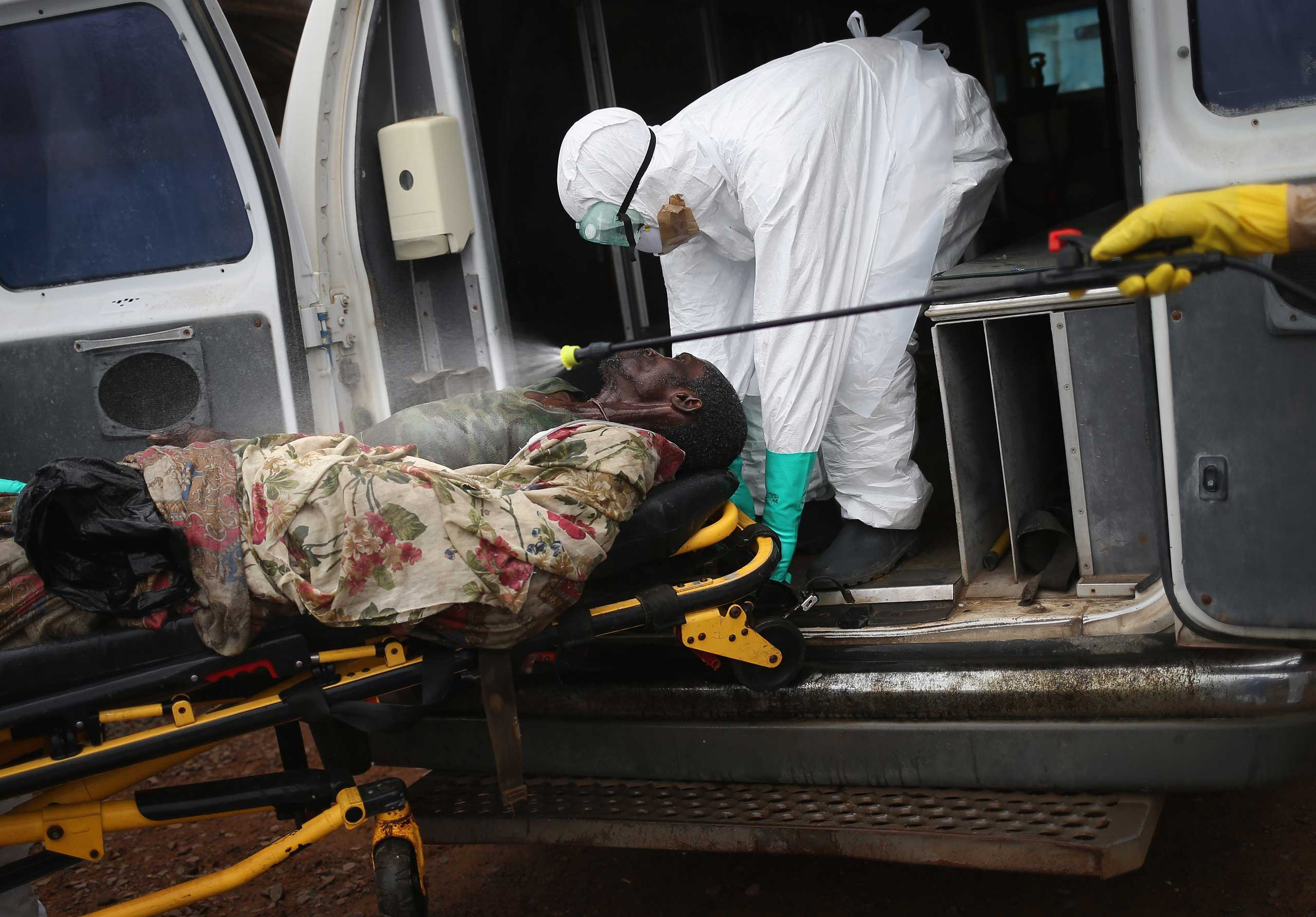 A burial team disinfects an Ebola victim while collecting him for cremation on Oct. 2, 2014 in Monrovia, Liberia.