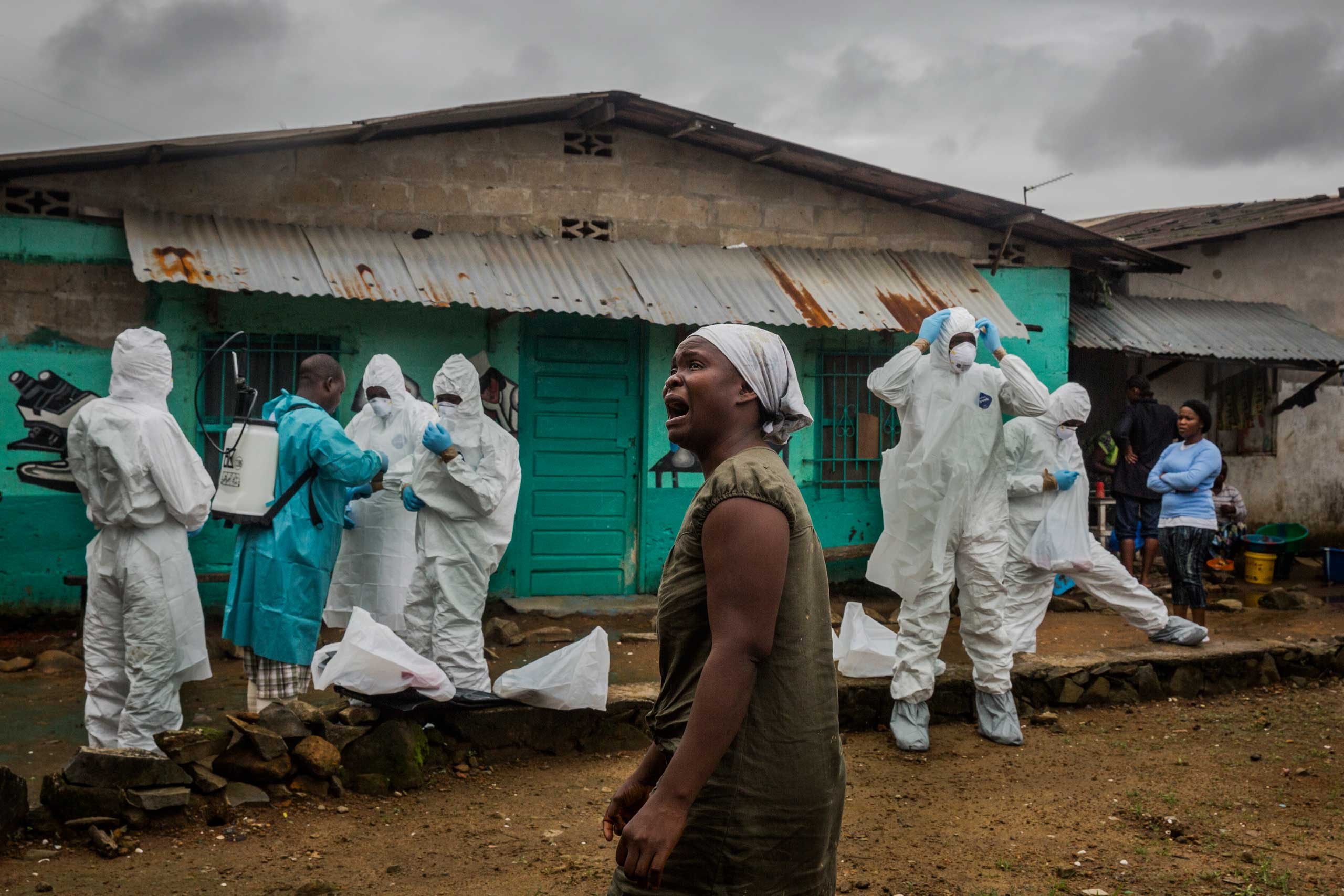 A relative grieves as members of a Liberian Red Cross burial team dress themselves in full protective clothing prior to removing the body of suspected Ebola victim, Ofori Gweah, 62, on Sept. 18, 2014 in central Monrovia, Liberia.