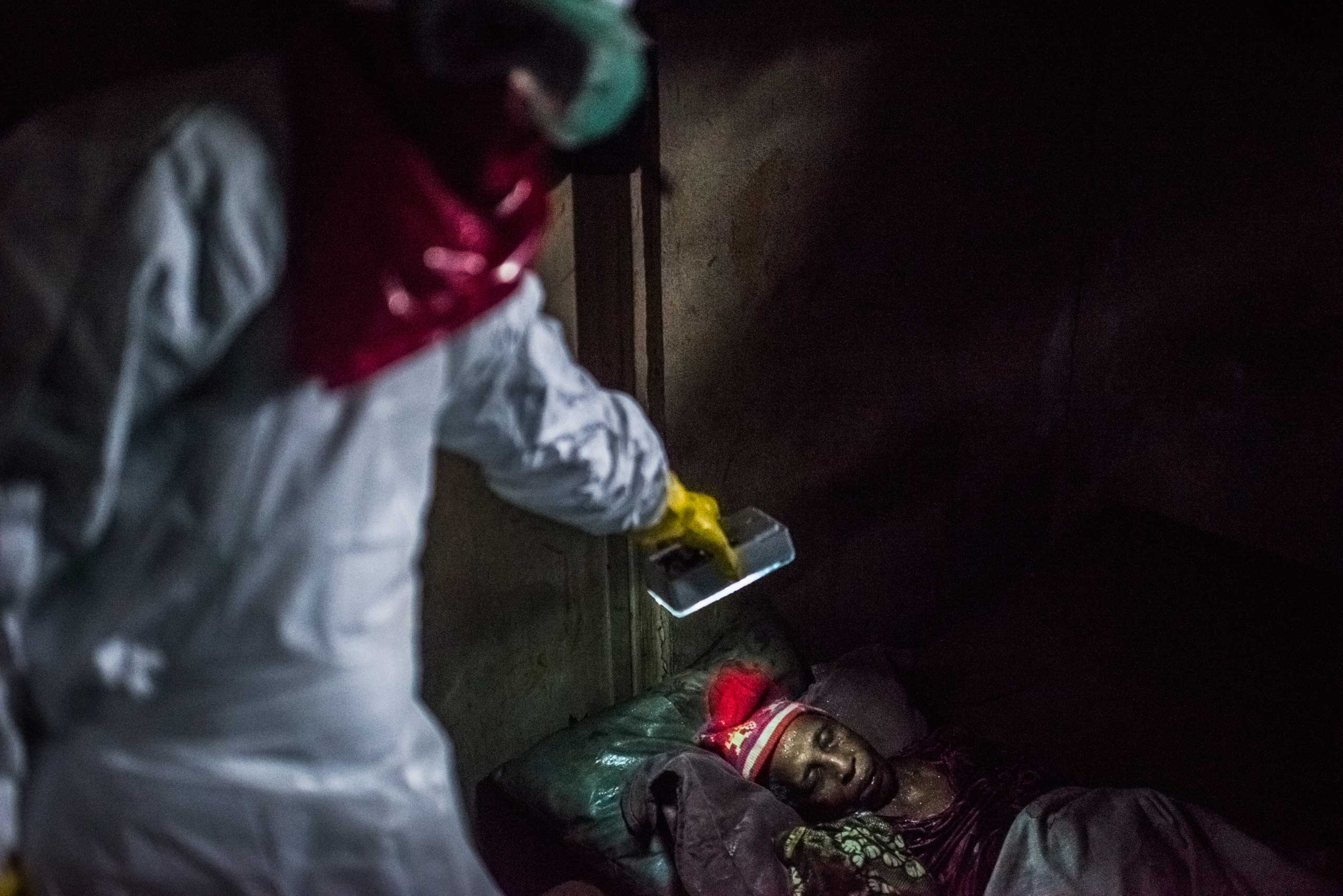Members of a Liberian Red Cross burial team, remove the body of woman, 75, a suspected Ebola victim on Sept. 18, 2014 in Monrovia, Liberia.