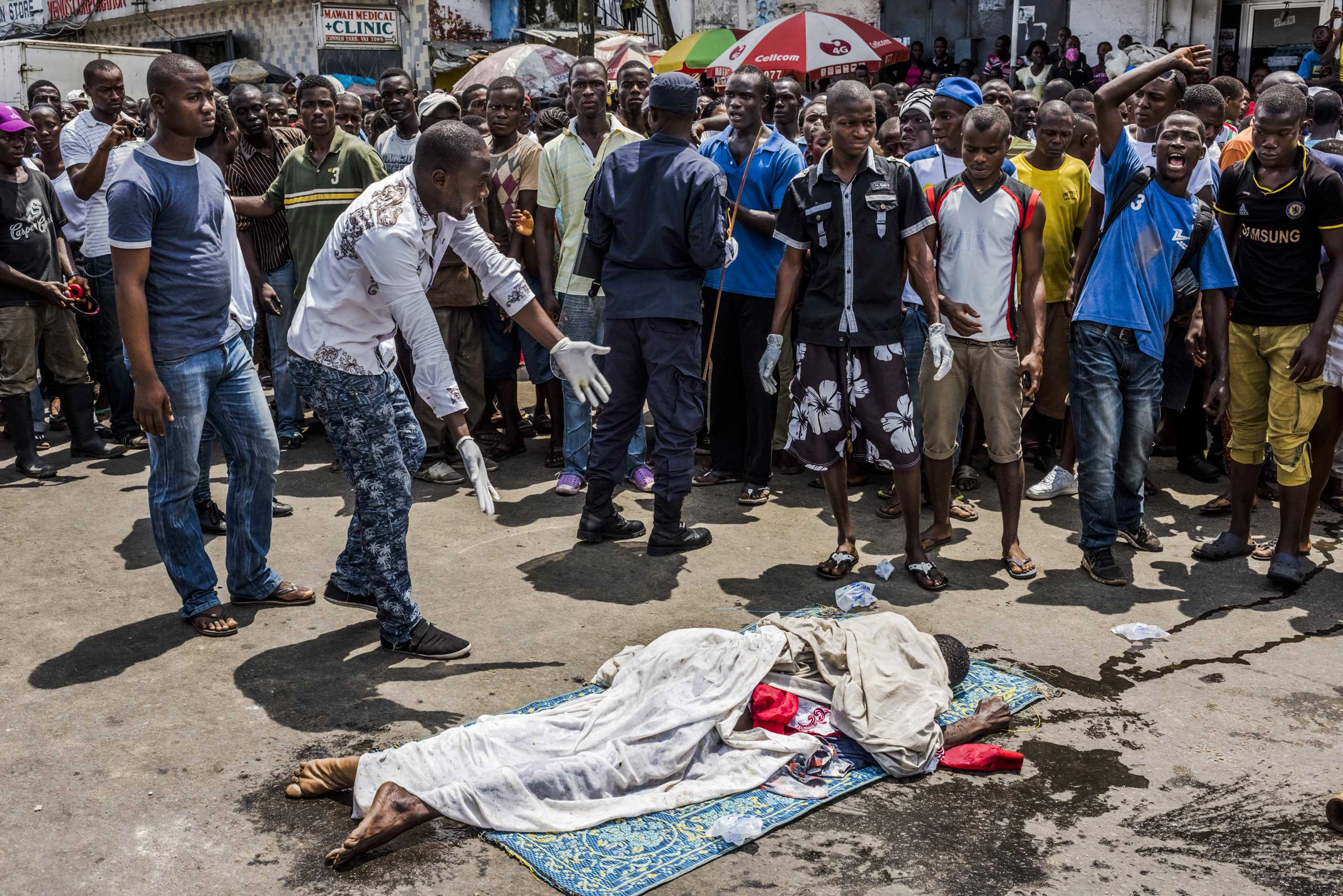 Residents look on as the body of a man suspected of dying from Ebola lies in a busy street after it was reportedly dragged there to draw the attention of burial teams. For several days, his family had asked for the body to be picked up, to no avail. Monrovia, Liberia, Sept. 15, 2014.