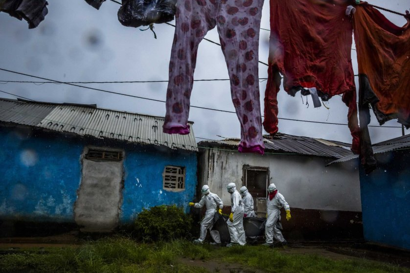 A burial team collects the body of a 75-year-old woman in a neighborhood called PHP in Monrovia, Liberia.