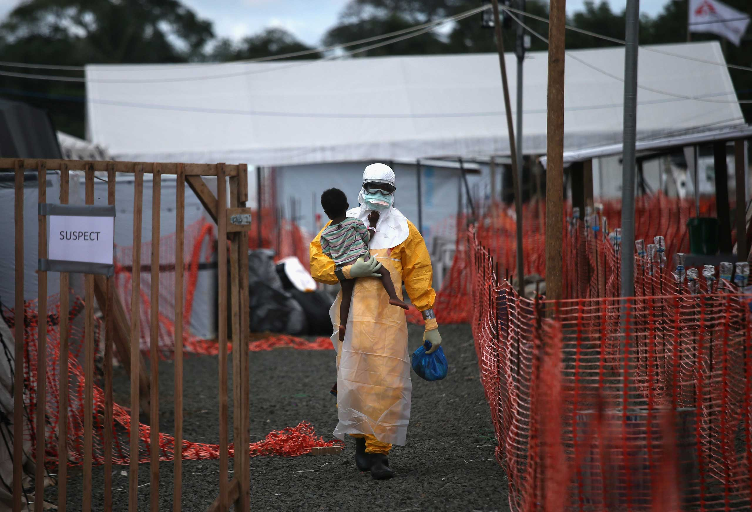 A Doctors Without Borders health worker in protective clothing carries a child suspected of having Ebola in the MSF treatment center on Oct. 5, 2014, in Paynesville, Liberia