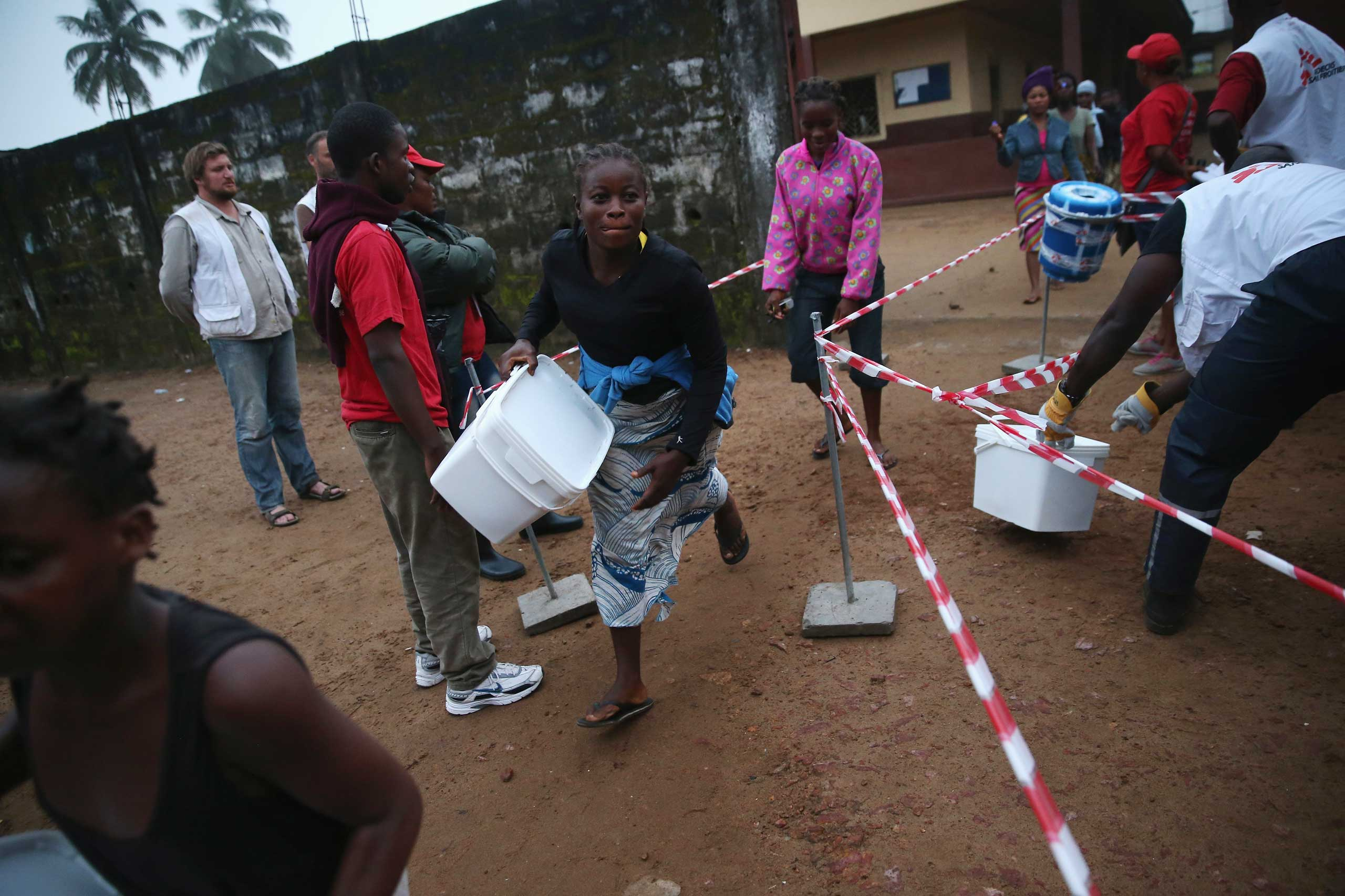 Residents take home family and home disinfection kits distributed by Doctors Without Borders, on Oct. 4, 2014 in New Kru Town, Liberia.