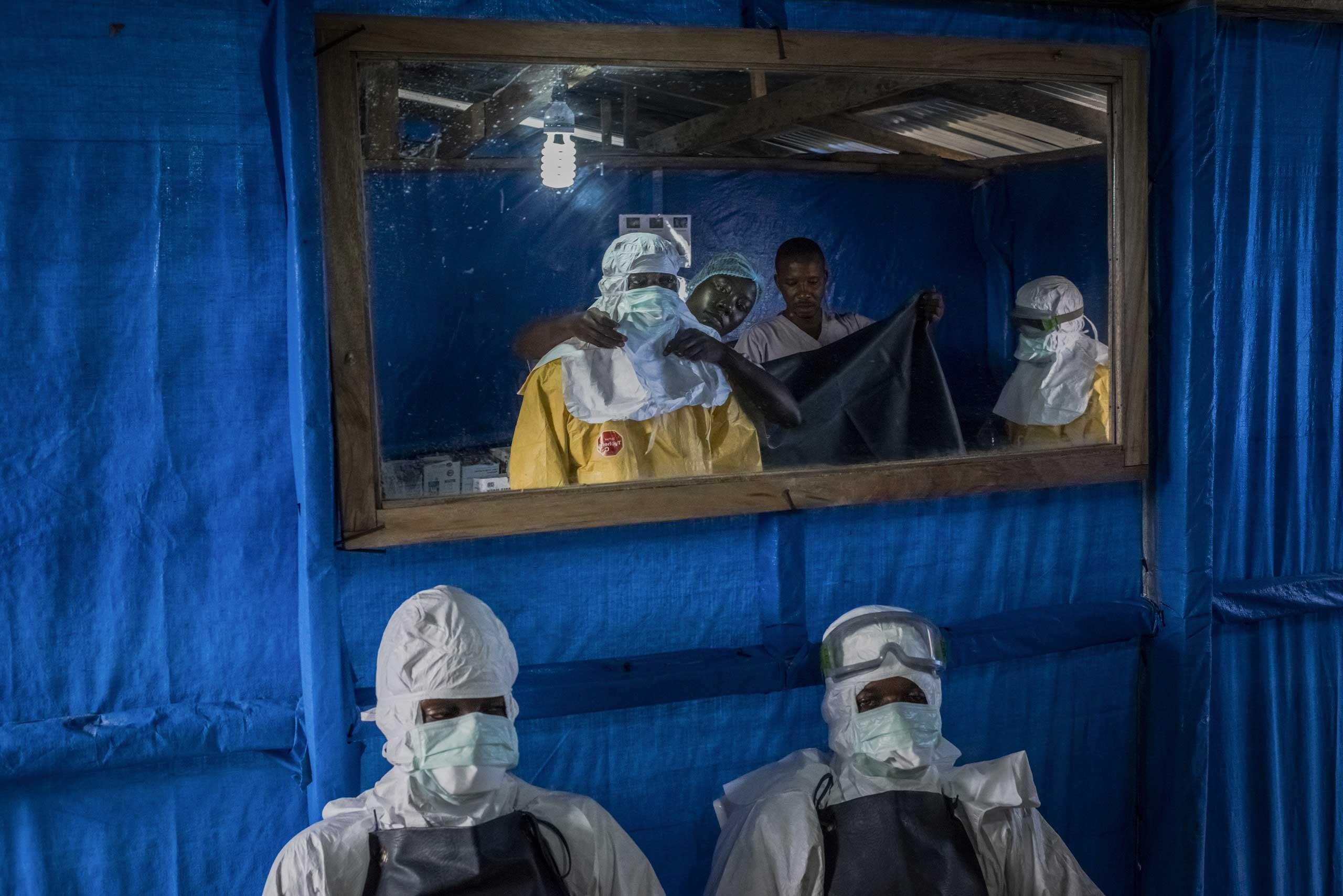 Health workers receive assistance with putting on their protective gear before entering the high-risk zone at the Bong County Ebola Treatment Unit near Gbarnga in rural Bong County, Liberia, Oct. 5, 2014.