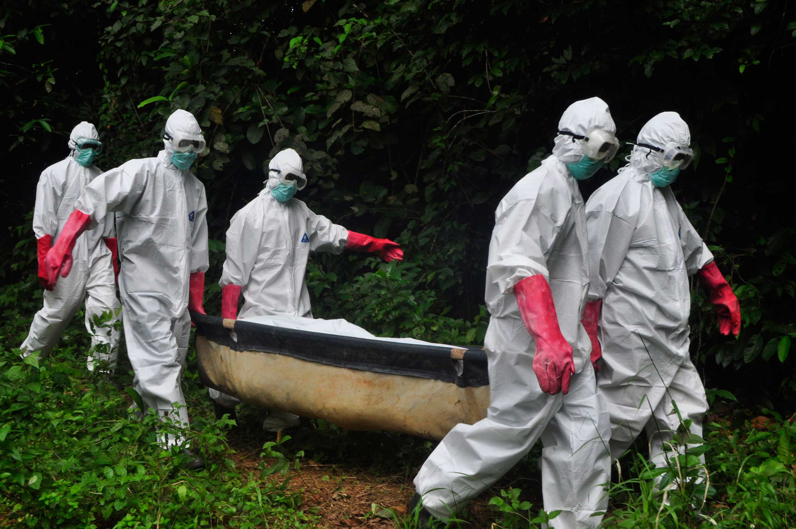 A burial team in protective gear carry the body of woman suspected to have died from the Ebola virus in Monrovia, Liberia, Oct. 18, 2014.