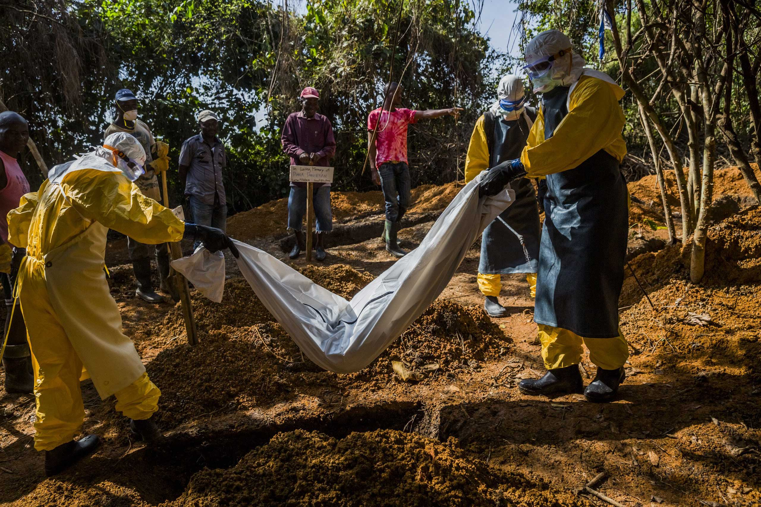 Members of a burial team wearing protective gear inter the body of 4-day-old Diana Dormeyan, named for her mother who died shortly after giving birth, at a graveyard adjacent to the Bong County Ebola Treatment Unit near Gbarnga, Liberia, Oct. 8, 2014.