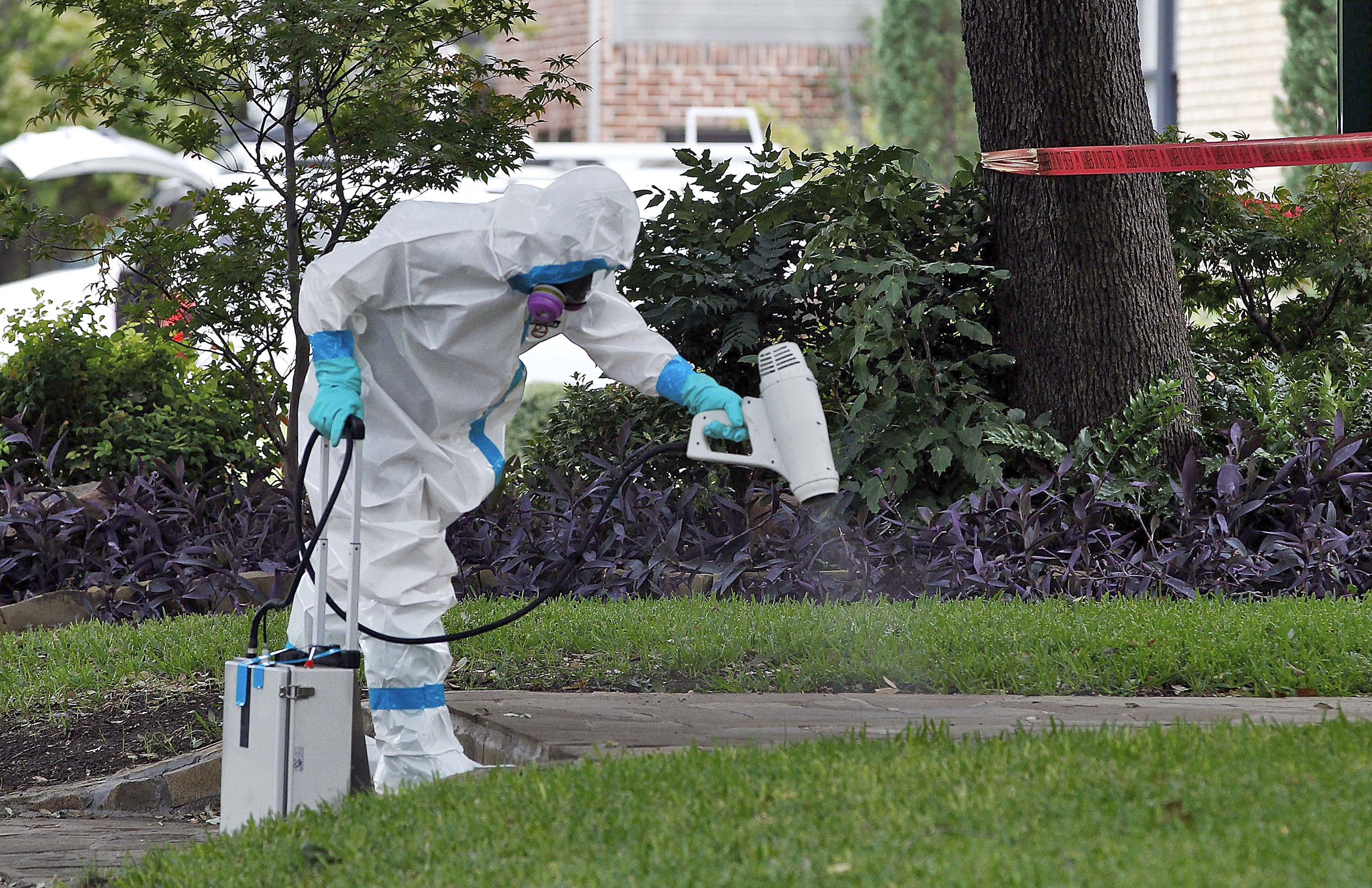 A worker disinfects the sidewalk outside the Dallas home of a nurse diagnosed with the virus