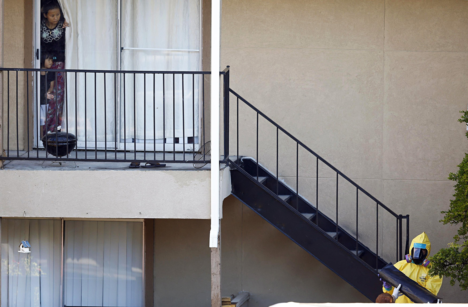 Neighbors watch as a biohazard team cleans the apartment where the Dallas Ebola patient stayed