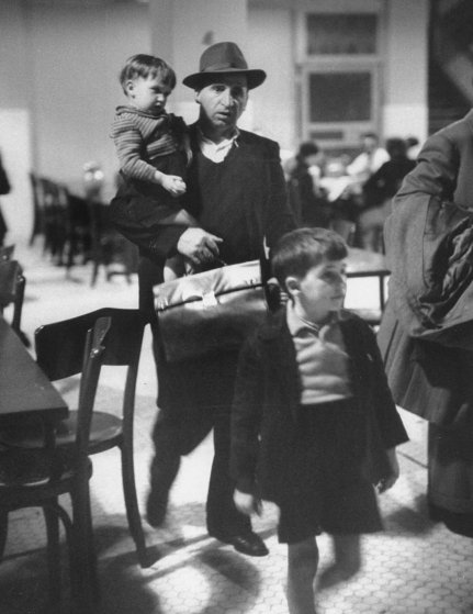 """""""Antonio Magnani copes with his children and fat briefcase holding his entry papers."""" Ellis Island, 1950."""