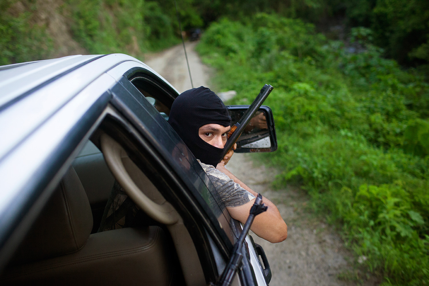 A member of an autodefensa group patrols a mountain road, Michoacán, Mexico,  July, 2013.