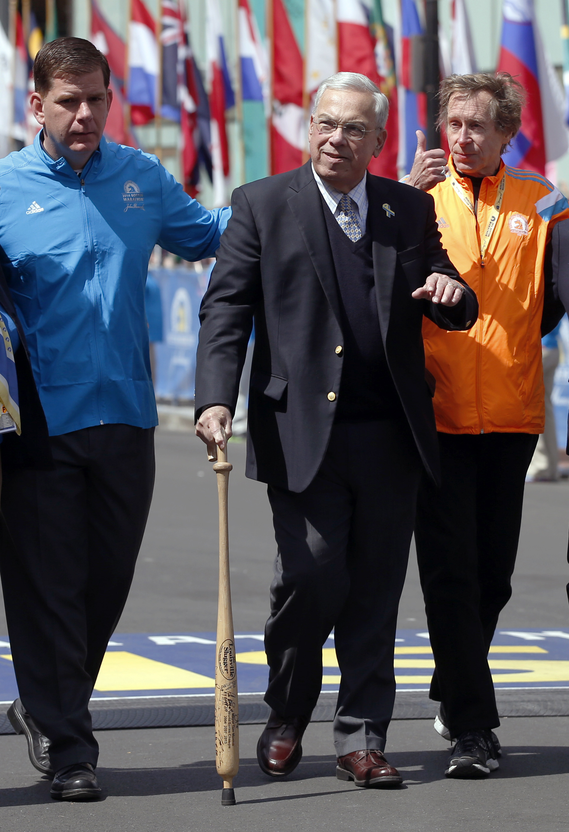 FILE - In this April 21, 2014 file photo, from left, Boston Mayor Martin Walsh, former Mayor Thomas Menino, and four-time Boston Marathon champion Bill Rodgers walk past the finish line before the start of the 118th Boston Marathon in Boston.