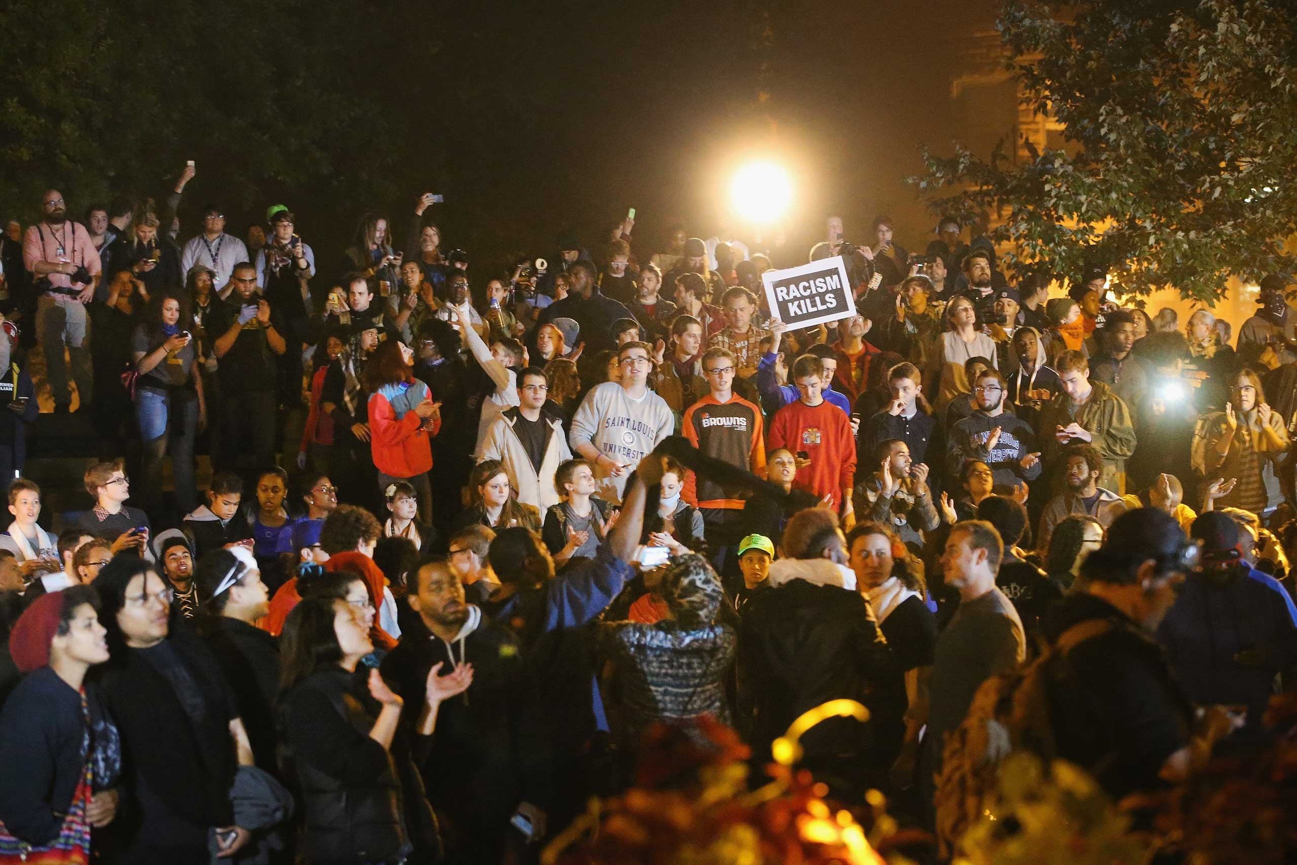 Demonstrators listen to speakers during a rally on the campus of St. Louis University in St. Louis on Oct. 13, 2014.