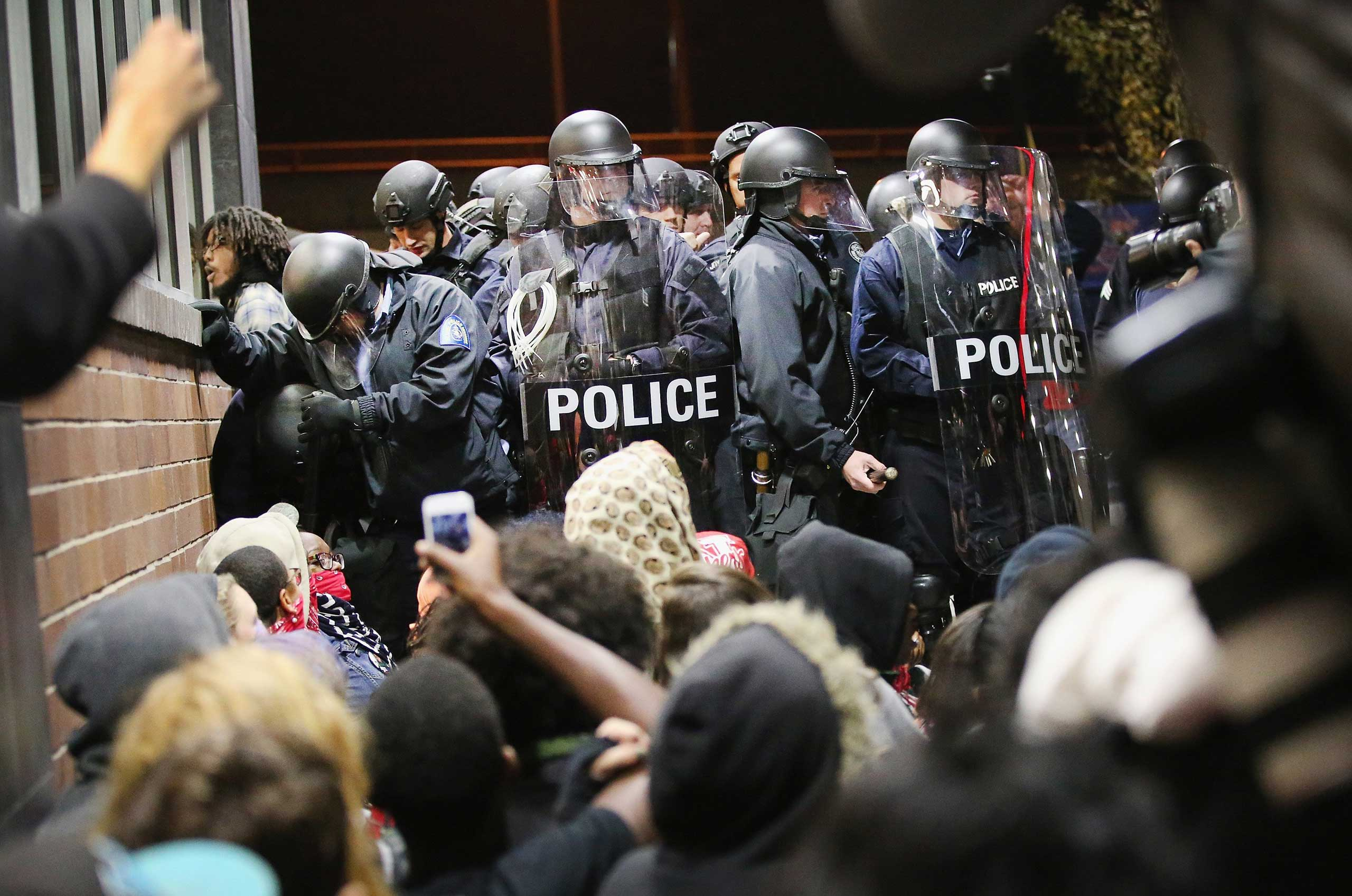 Police arrest demonstrators protesting the killings of 18-year-olds Michael Brown and Vonderrit Myers Jr. in St. Louis on Oct. 12, 2014.